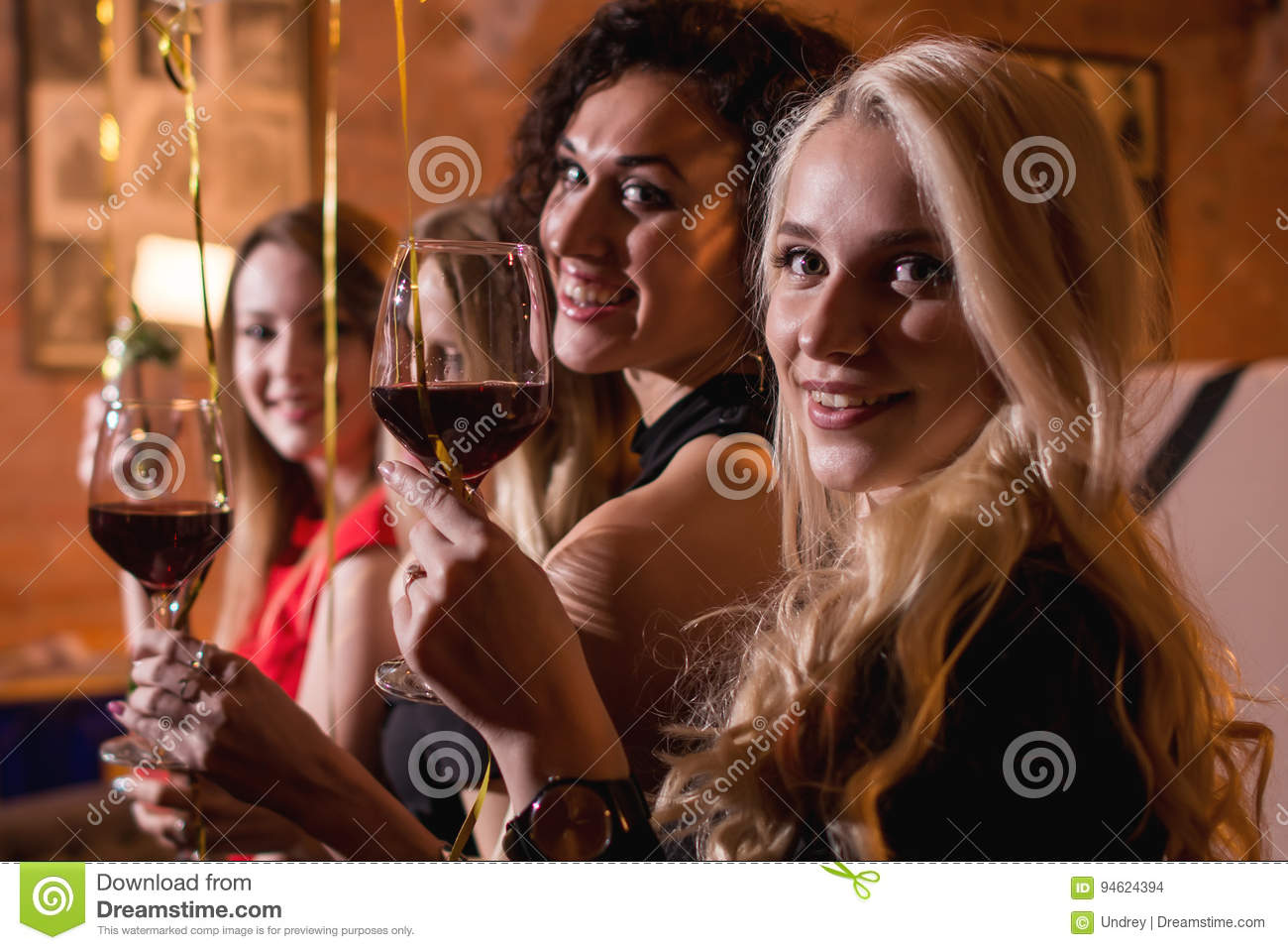 Close-up shot of positive beautiful female friends raising glasses of wine to happy event sitting in fashionable