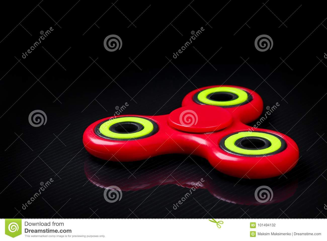 Close-up shot of red-green fidget finger spinner on black gloss background.