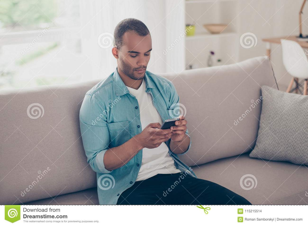 Close up shot of young concentrated black american guy, browsing