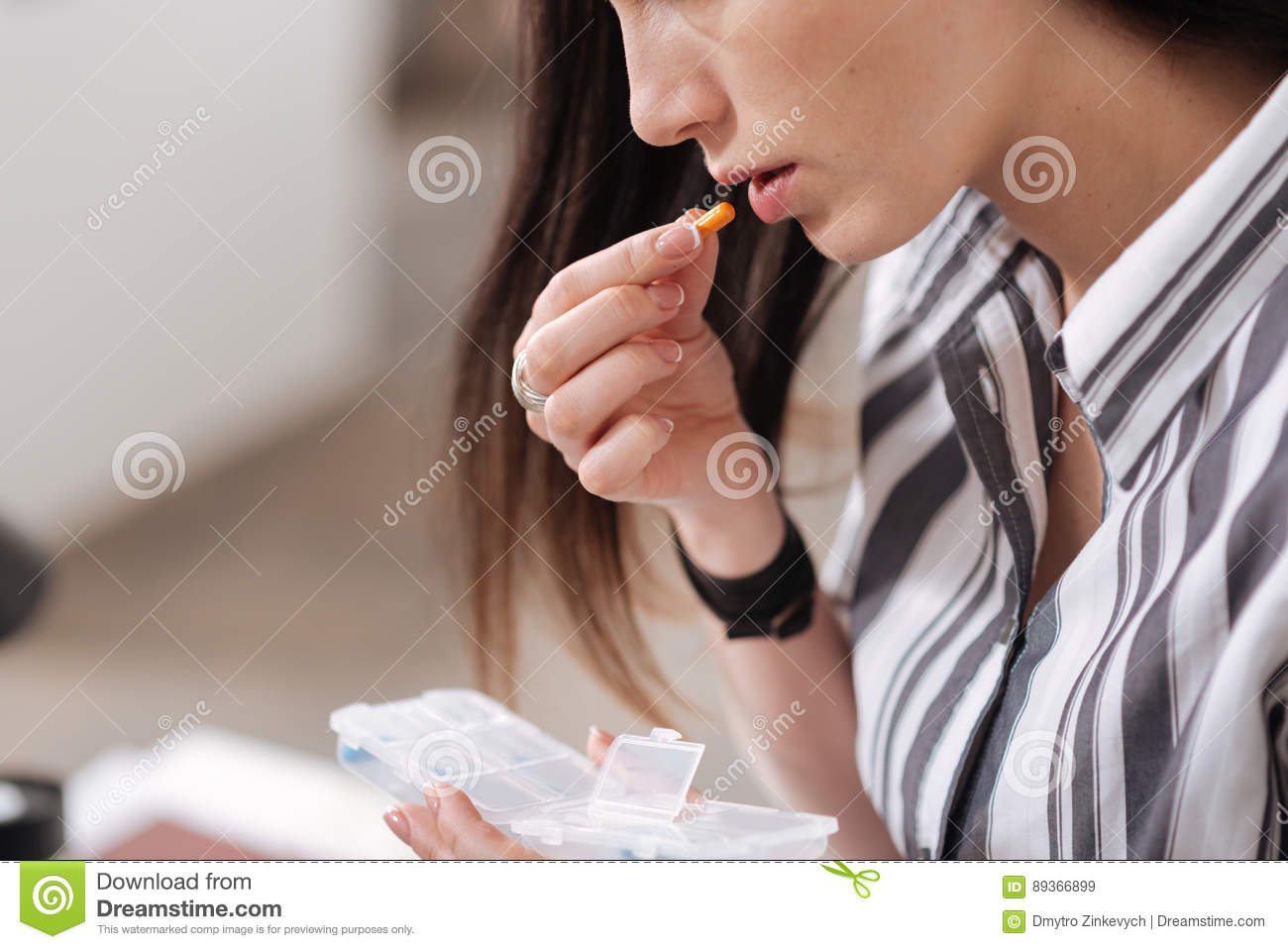 P O Of Office Worker That Wearinged Shirt Rising Right Hand With Orange Tablet To Mouth While Sitting In Semi Position