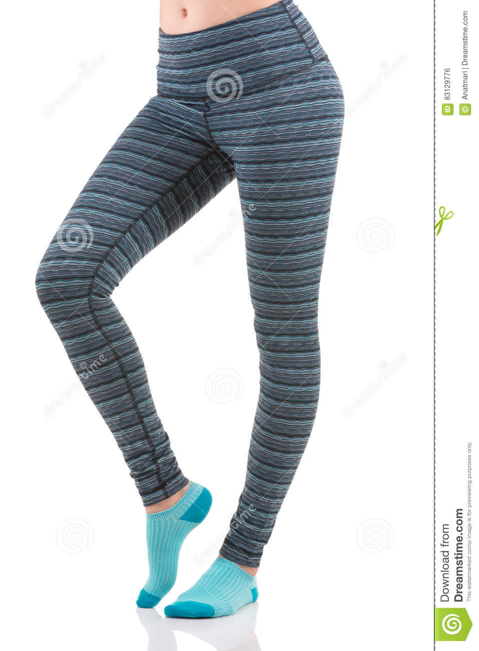 f99ed1a40ef6d Close up side view of fit woman legs warming up in colorful striped sports  leggings wearing blue socks on white isolated background