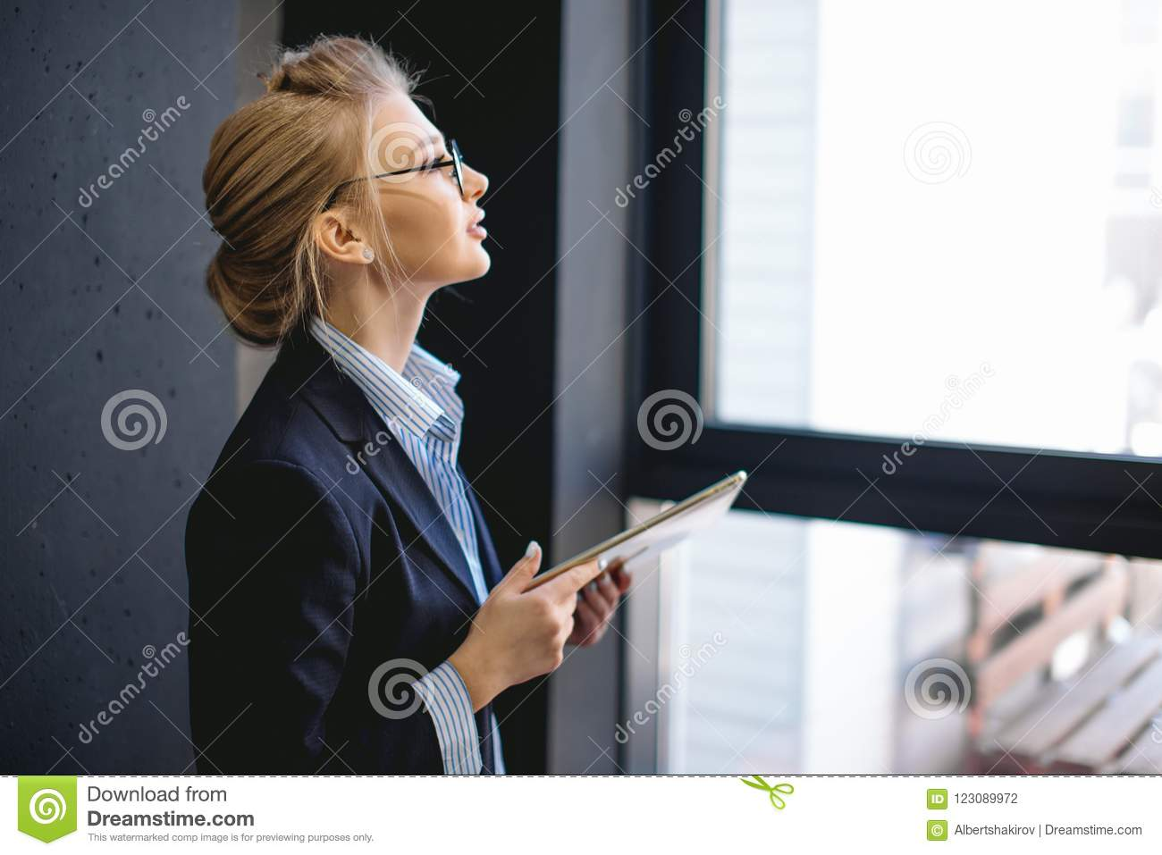 Pleasant woman with fair hair holding her laptop and looking at the window