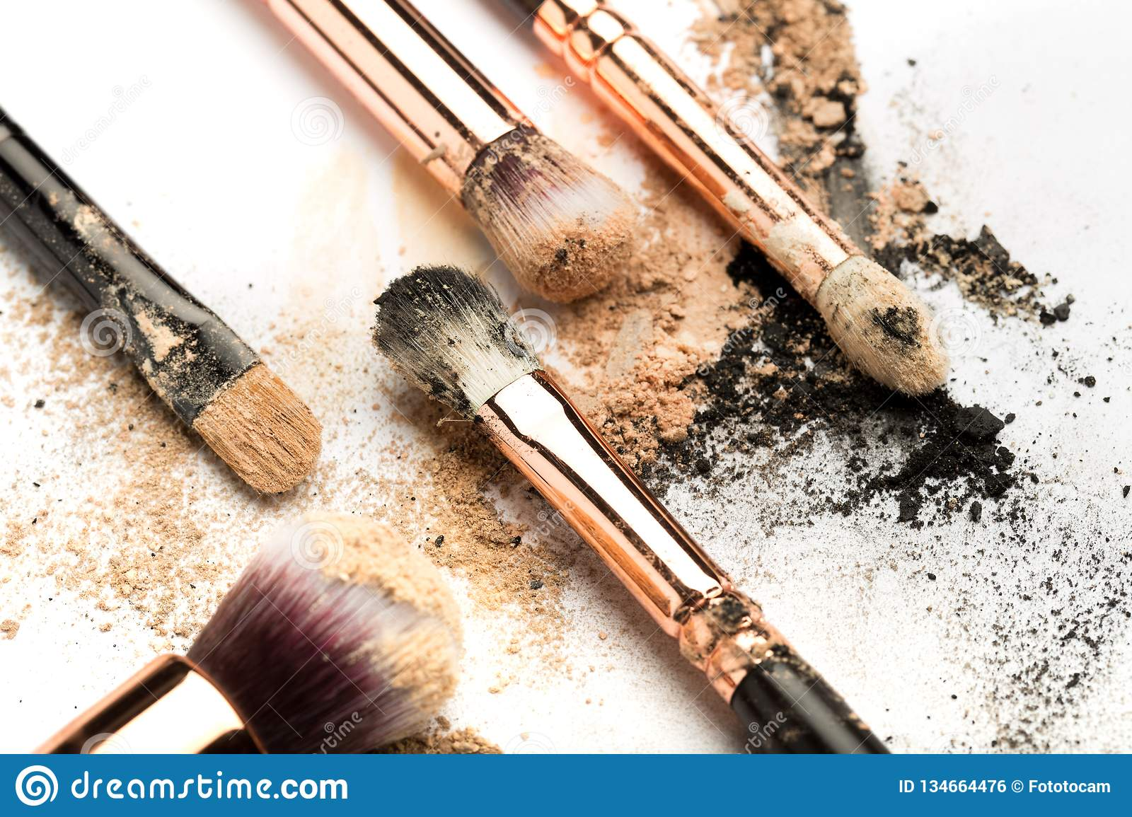 Close-up side view of professional make-up brush with natural bristle and black ferrule with crashed eyeshadow on white