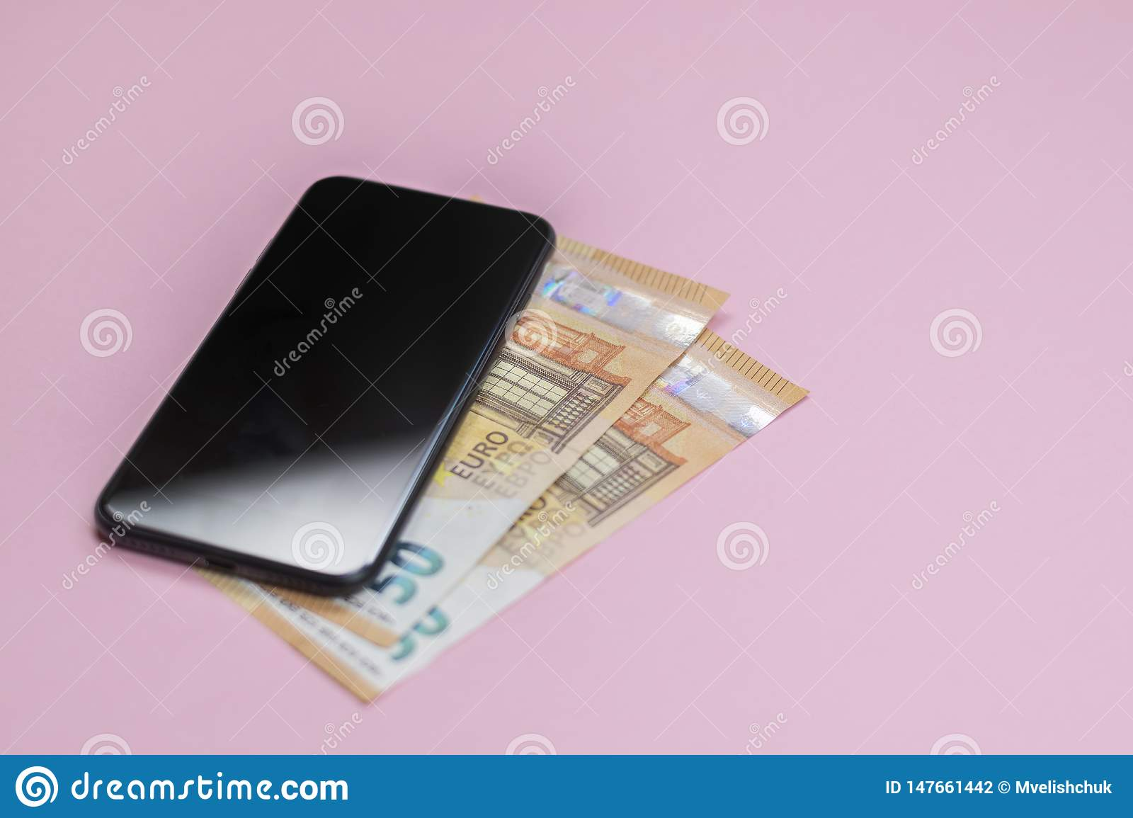 Close-up of smart phone with money on a pink background.