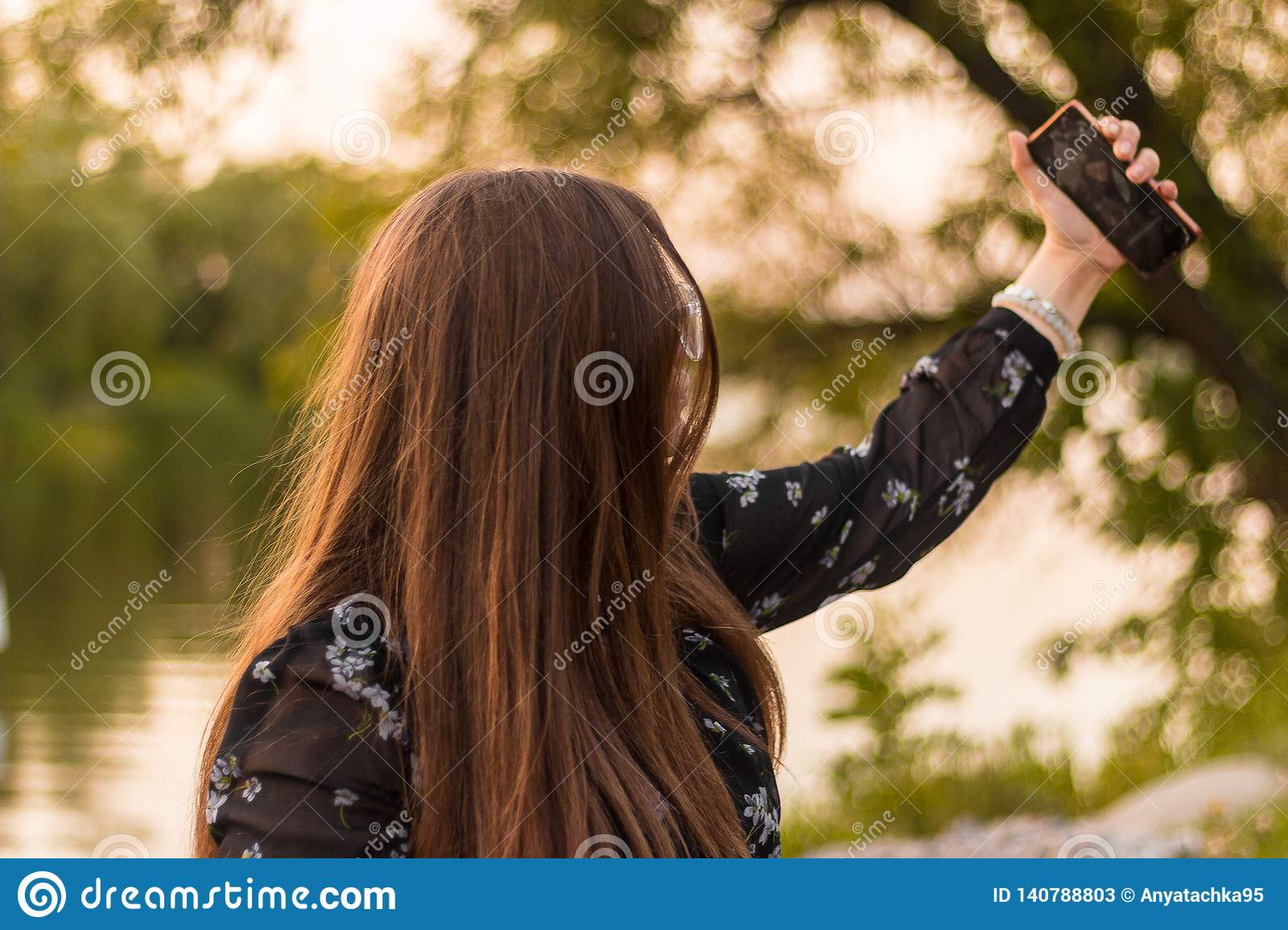 Cheerful girl making selfie on in park. Close up smiling girl photographing selfie on phone, girl is unfocused
