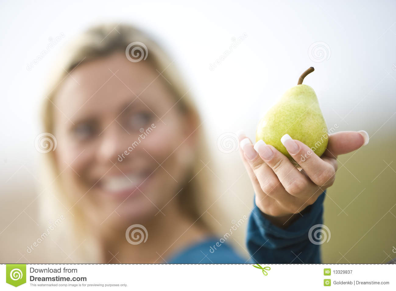 Close-up of smiling woman holding a pear