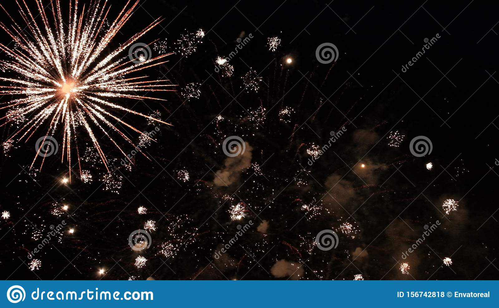Smoke and fiery flashes of a festive firework on a black background. Abstract background of the dark sky with a salute of the new