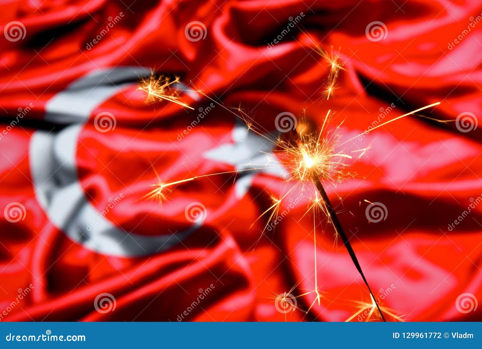 Close up of sparkler burning over Turkey, Turkish flag. Holidays, celebration, party concept.