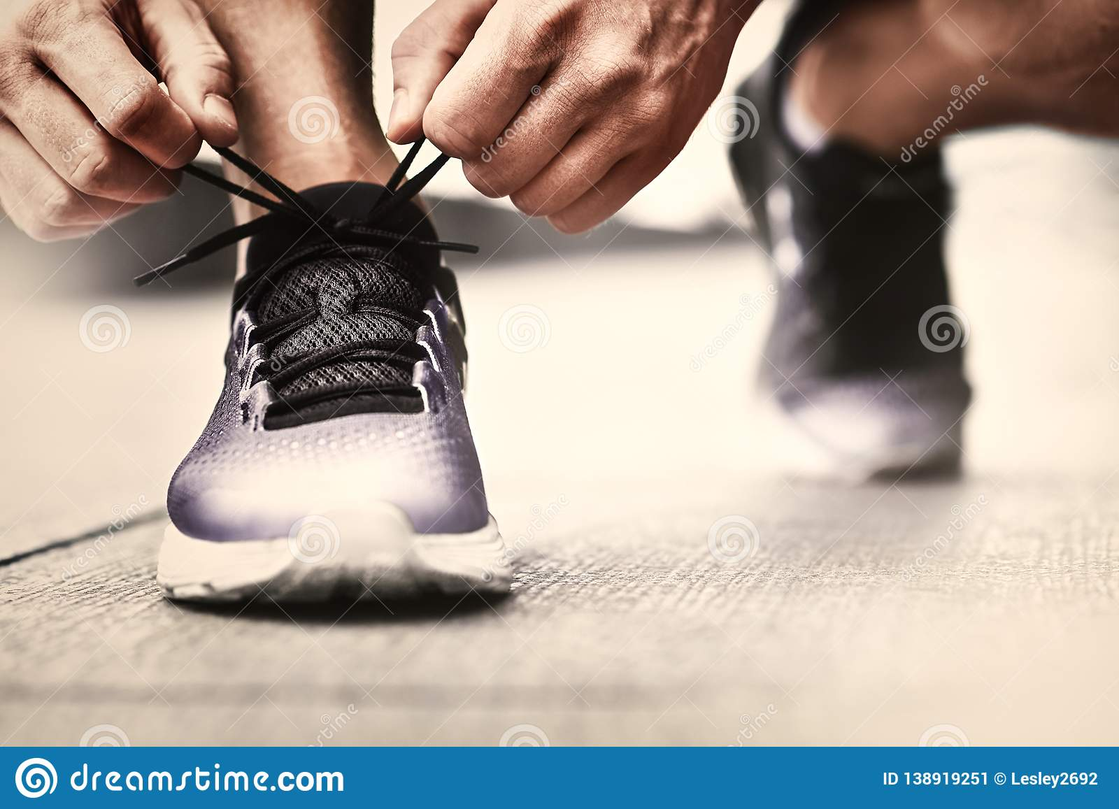 7b9f80311d4c Hands of sportsman with pedometer tying shoelaces on sporty sneaker. Running  equipment concept. Shoelaces tying by male hands
