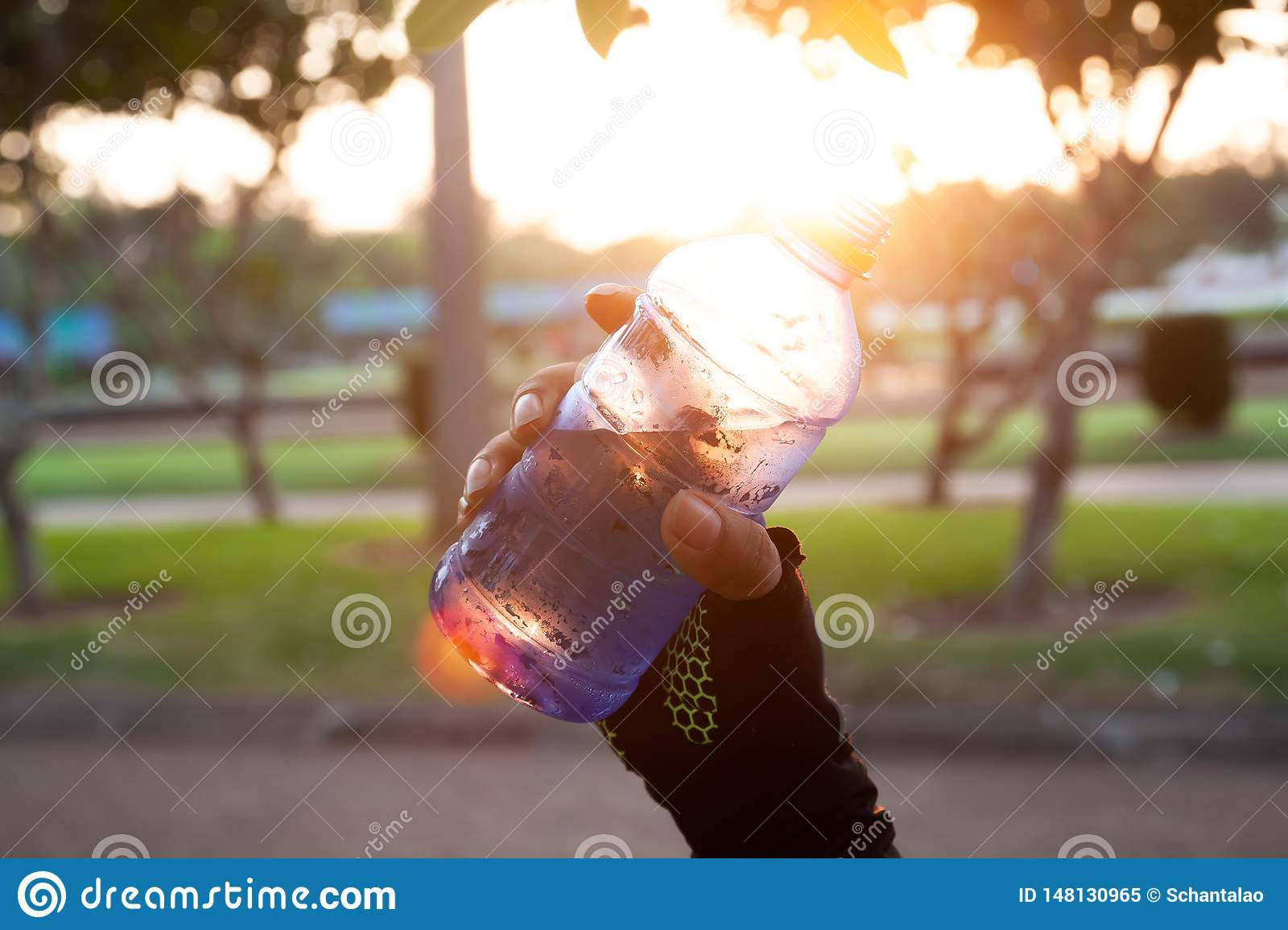 Close up sporty woman hand holding mineral water with sunset light