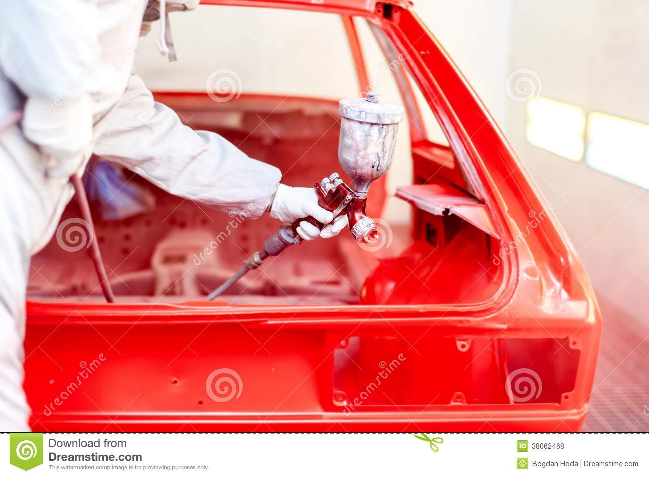 Close up of spray paint gun with worker working on a red for Spray paint on car