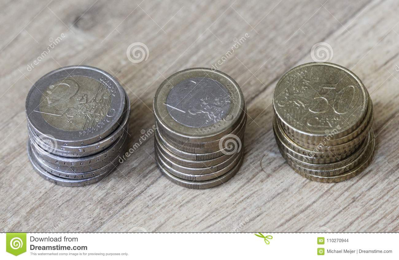 Stack Of Euro Coins From Big To Small On Wooden Background