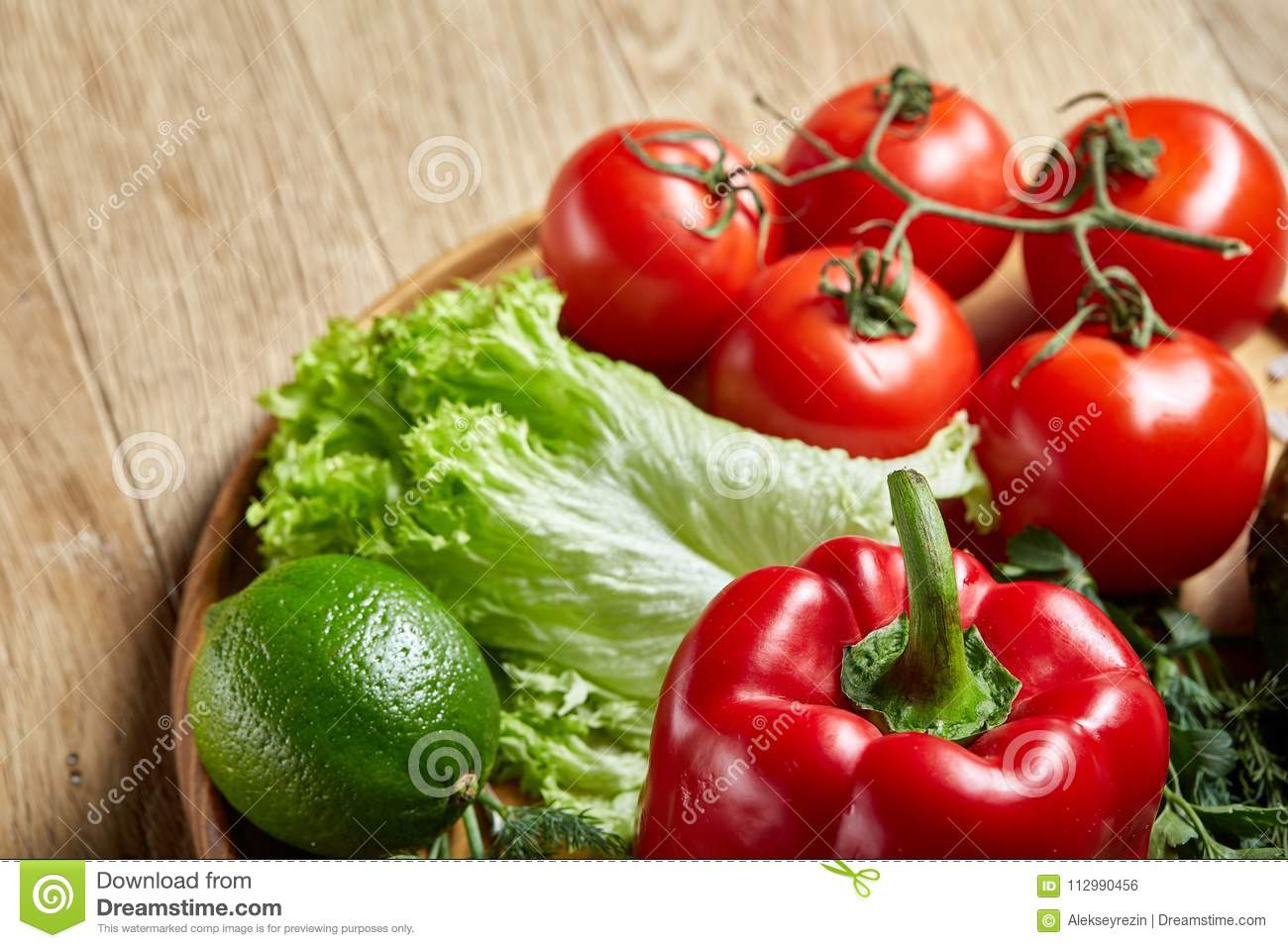 Close-up still life of assorted fresh vegetables and herbs on vintage wooden background, top view, selective focus.