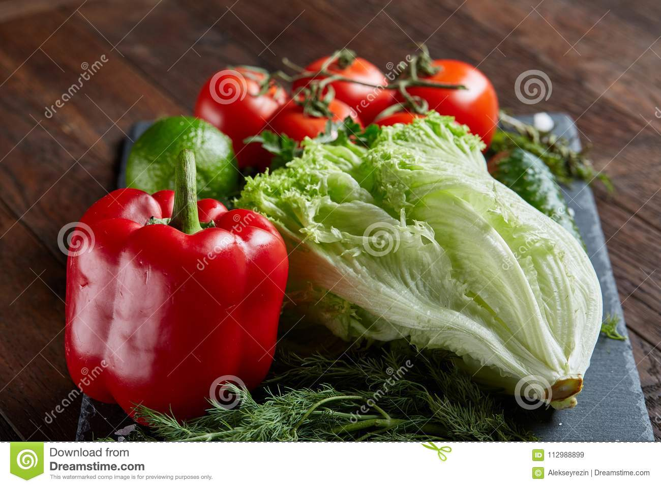 Close-up still life of assorted fresh vegetables and herbs on wooden rustic background, top view, selective focus.