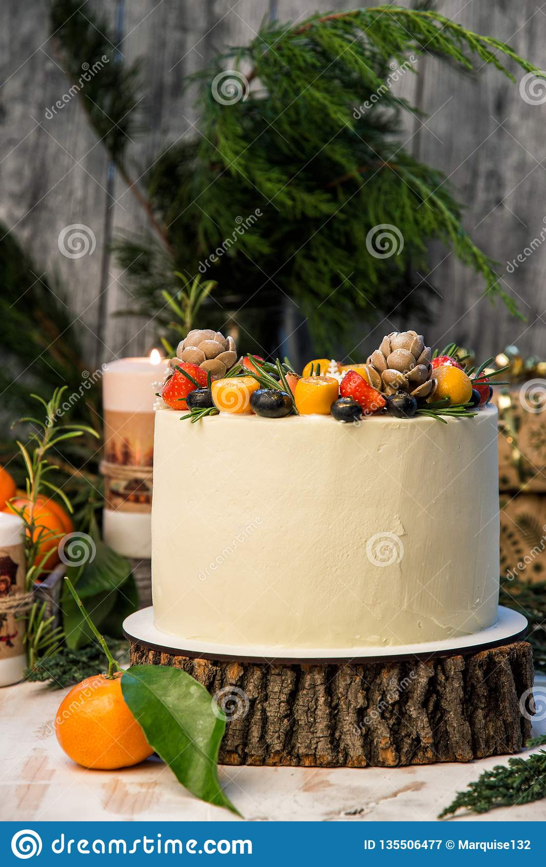 Close up. New Year`s Cake, decorated various berries. Gray wooden background, junipes branches