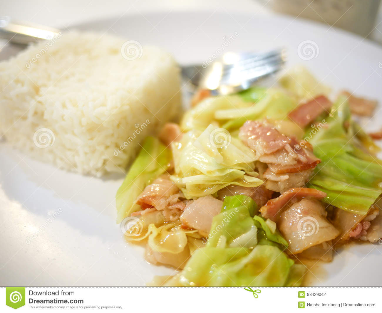 Close up stir fired cabbage and bacon with jasmine rice on white plate
