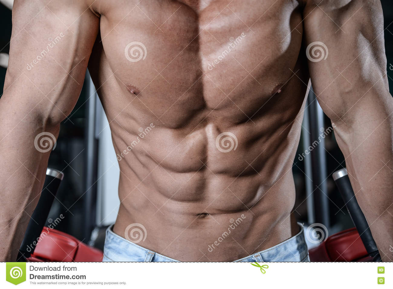 Close up strong abs guy showing in the gym muscles