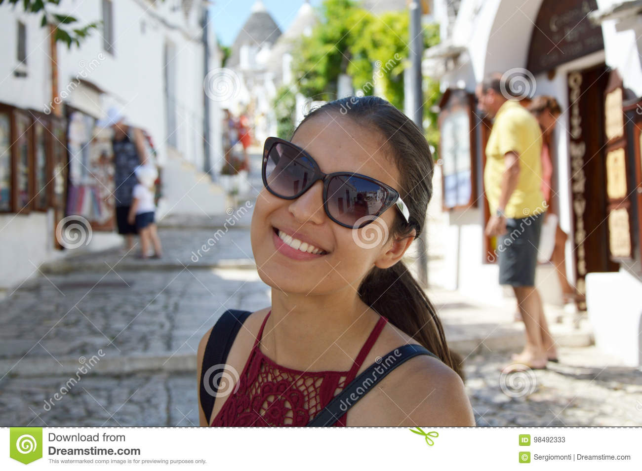 Close up of stylish young woman with sunglasses smiling in italian scenery background. Beauty woman with white perfect smile looki
