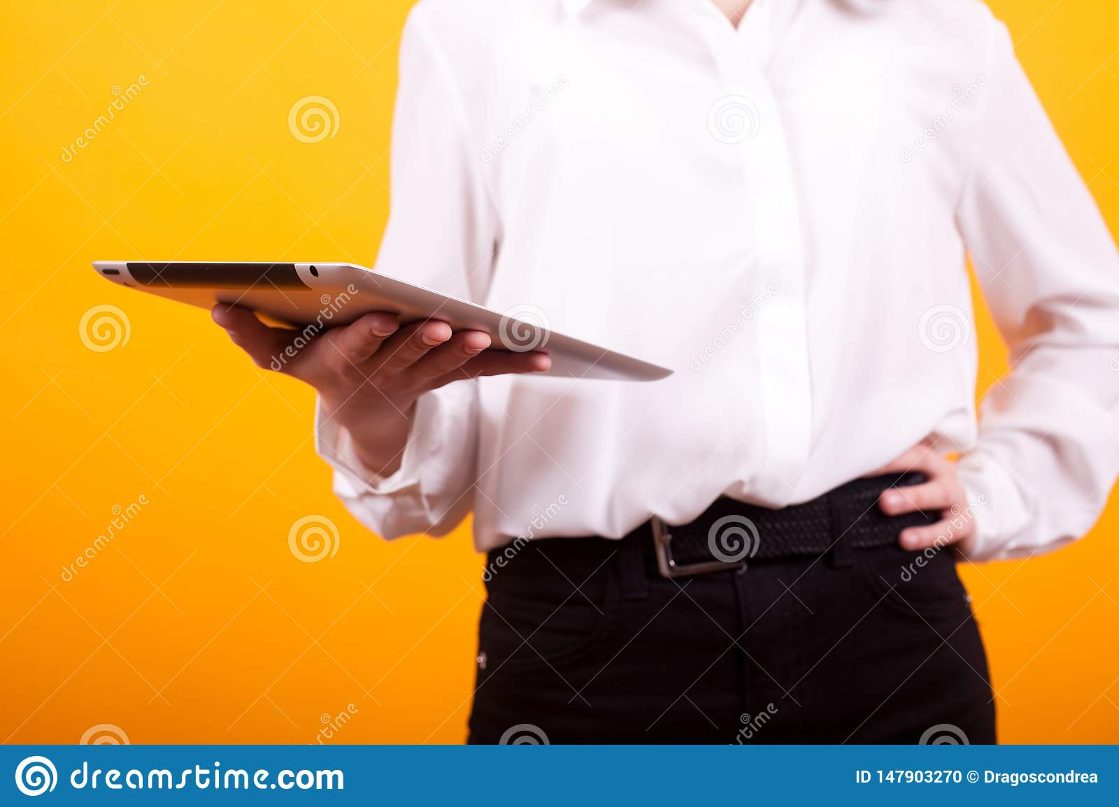 Close up of teenage girl holding a tablet  in studio over yellow background