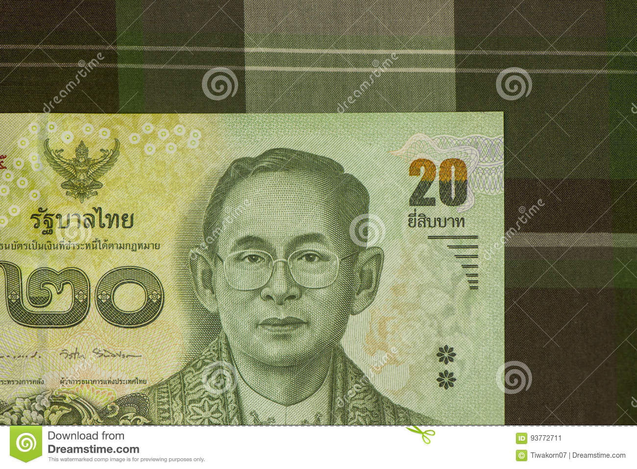 Close up of Thai banknote Thai bath with the image of Thai King. Thai banknote of 20 Thai baht on Green Scottish fabric.