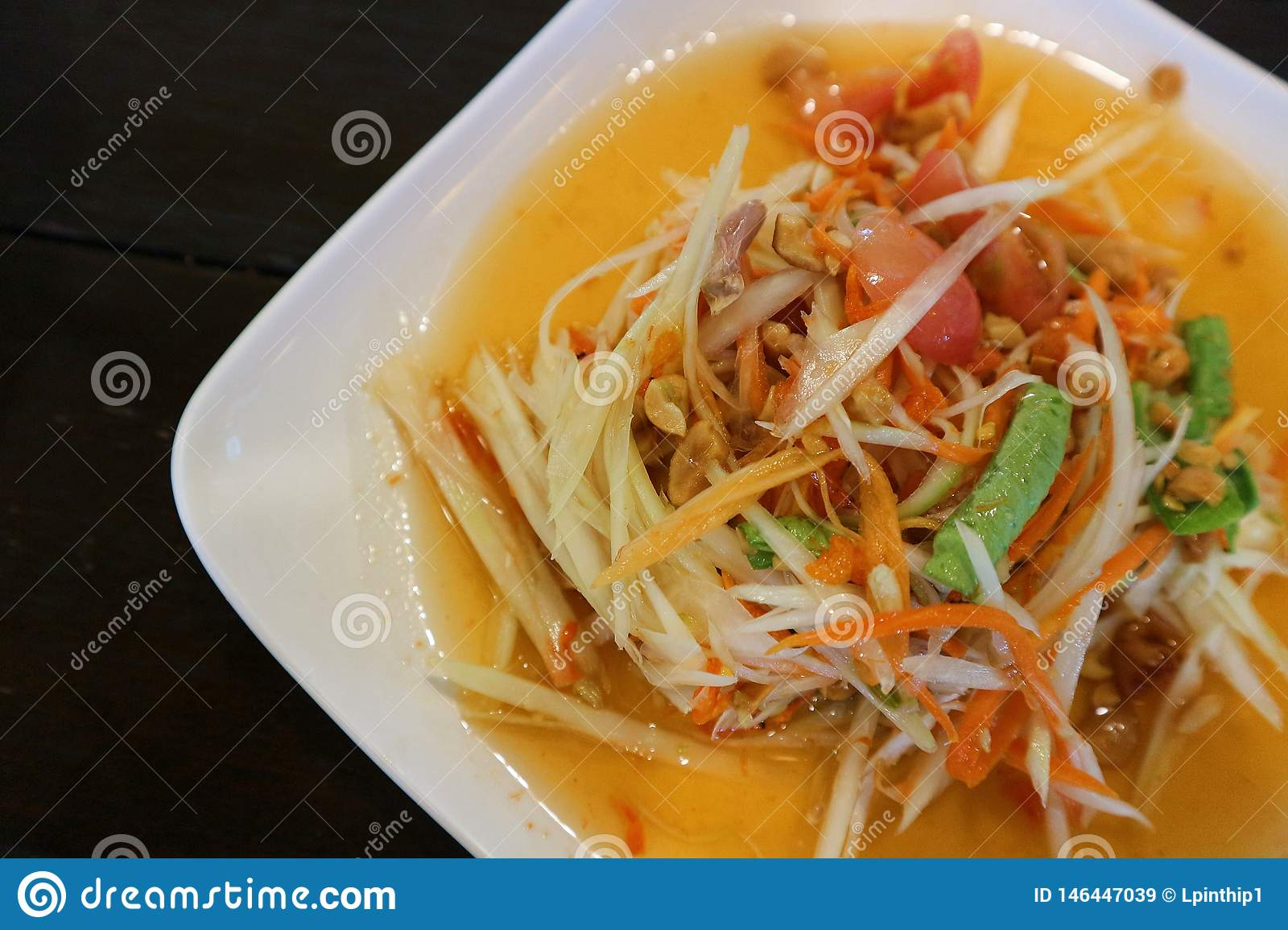 Close up Thai papaya spicy salad or som tum in white plate and black background