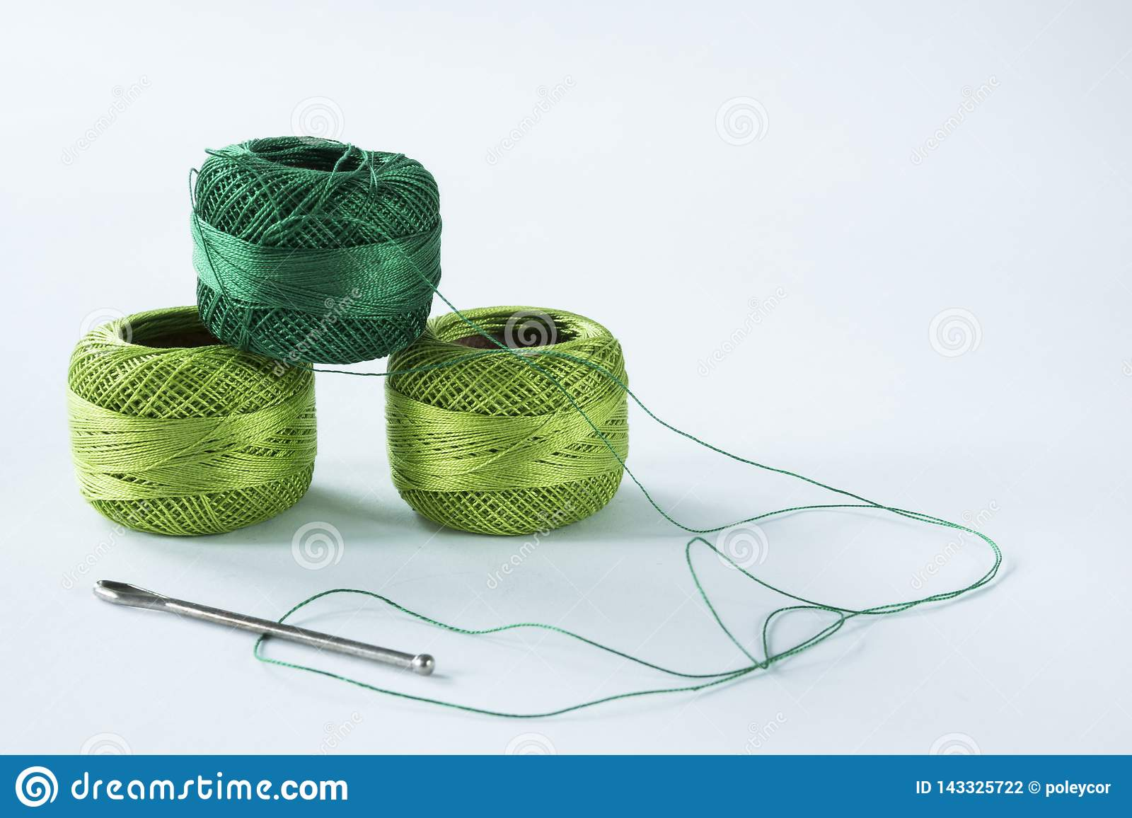 Green crochet yarn with scissors and needle. White background,