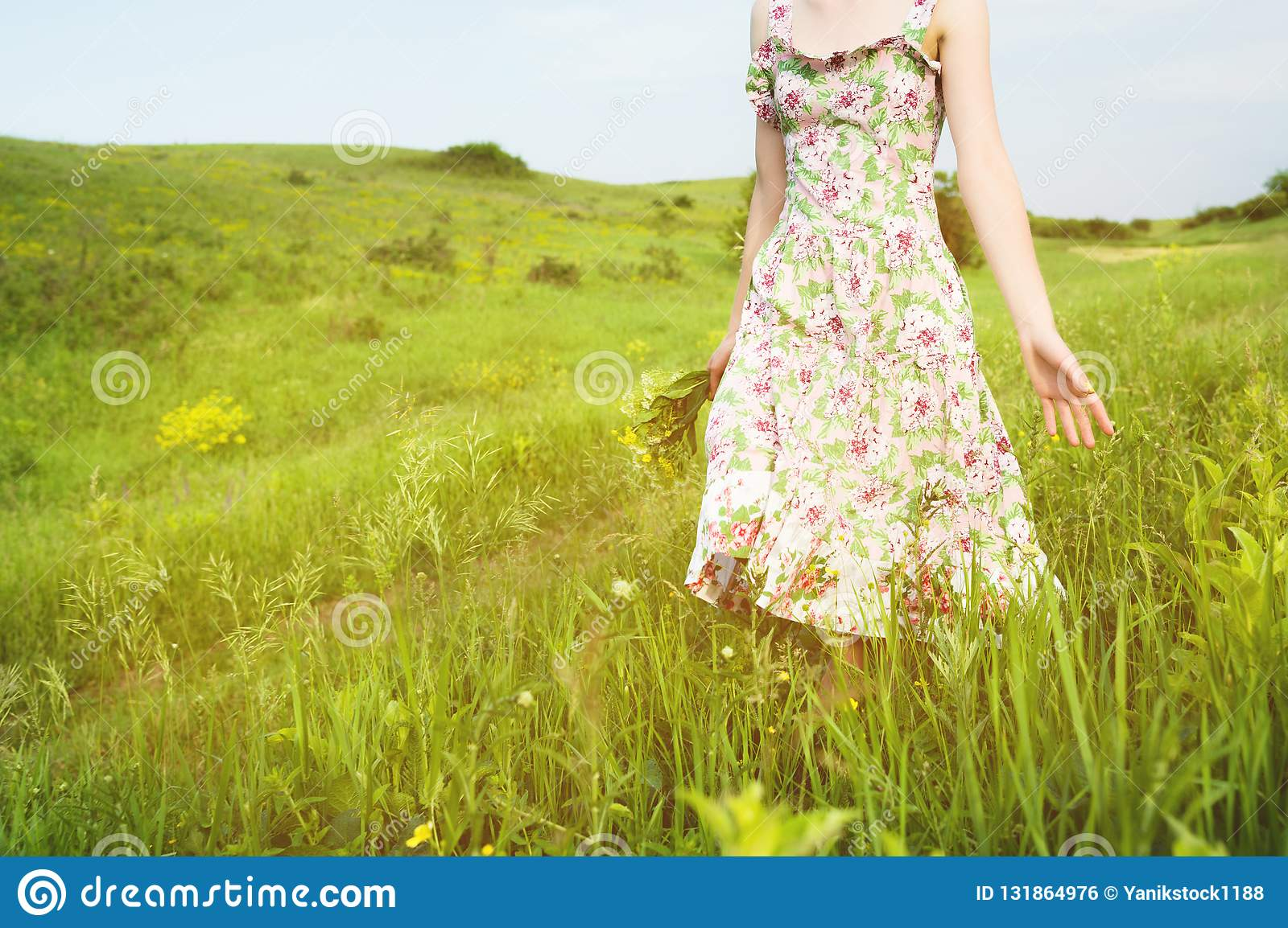 Close-up to the shoulders from below a young girl with a bouquet of wild flowers in her hand walks along a country road
