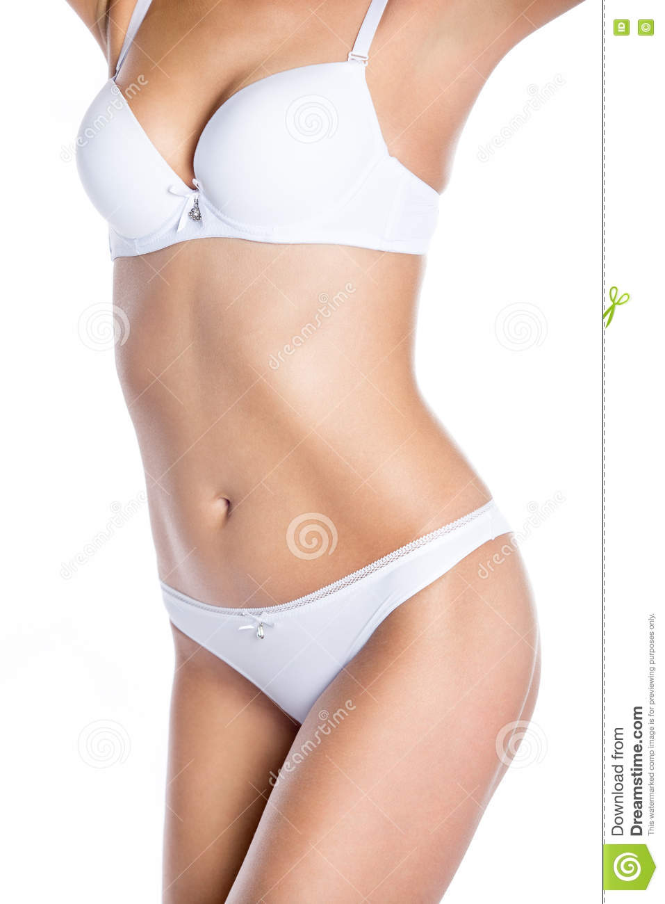 Close-up of torso of beautiful attractive Caucasian young woman wearing  white set of lingerie. Fashion girl in white bra and panties standing  against white ... eb9f4f1b6