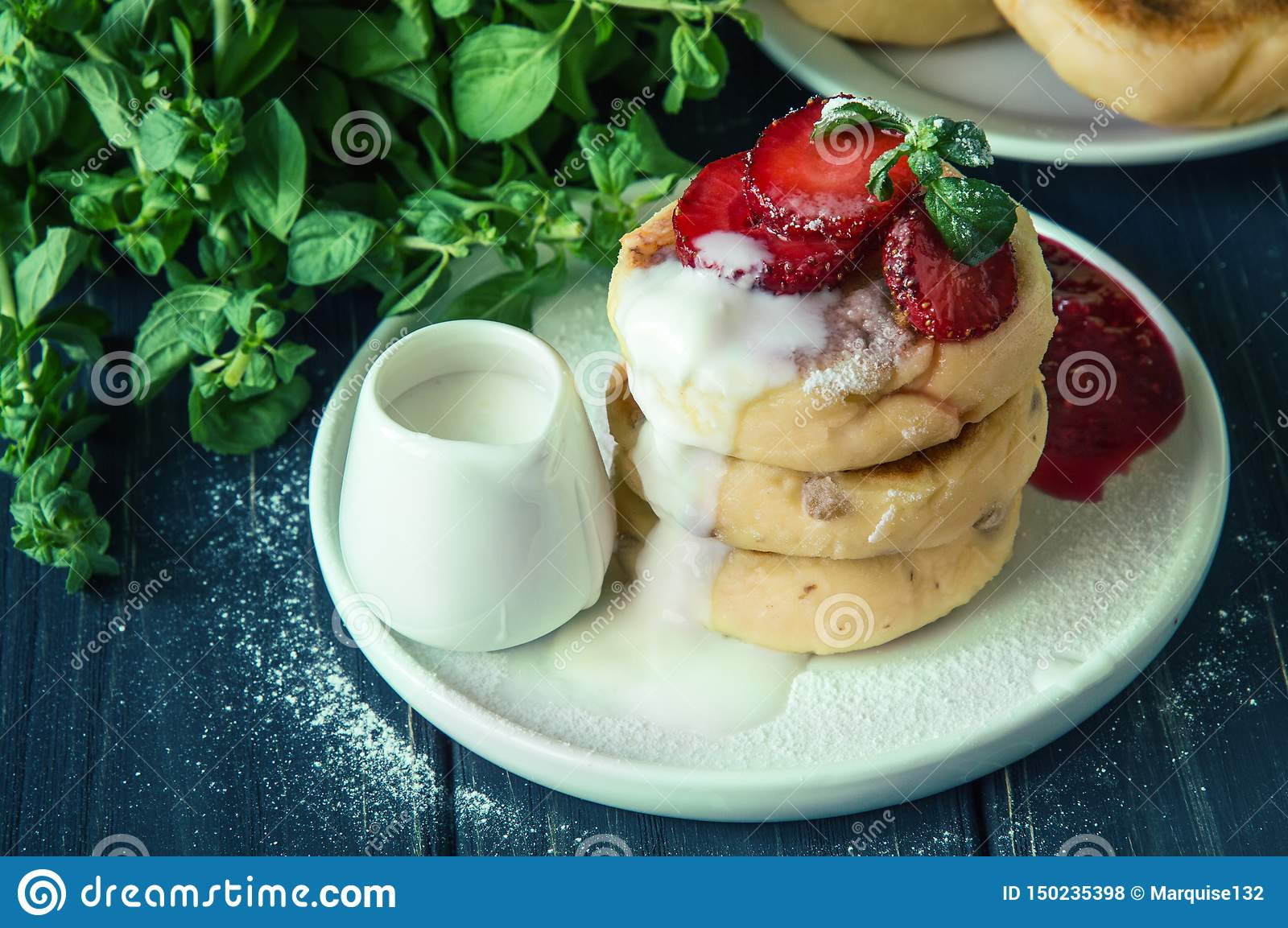 Close up. Traditional rustic breakfast. Freshly made cheese pancakes, poured with cream and decorated with strawberries. Copy