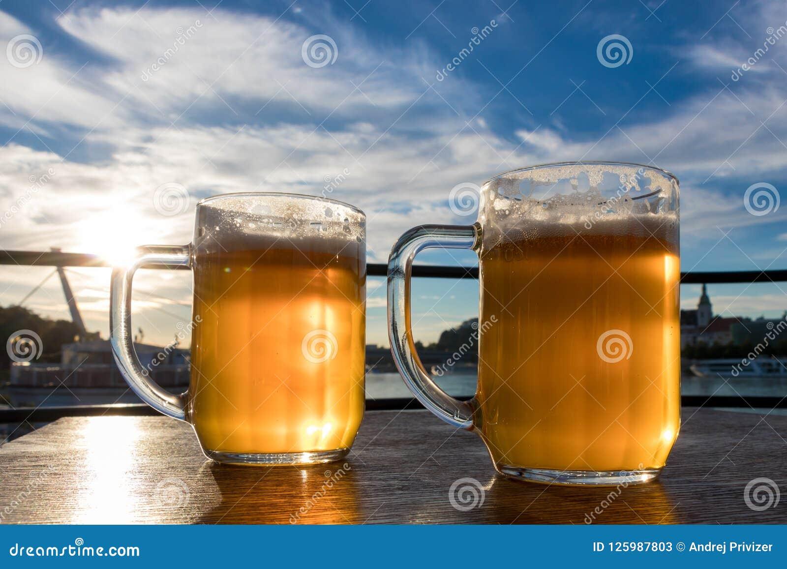 Close-up twee koude bieren met schuim en waterdalingen op de blauwe hemel als achtergrond en de witte wolken en de zon