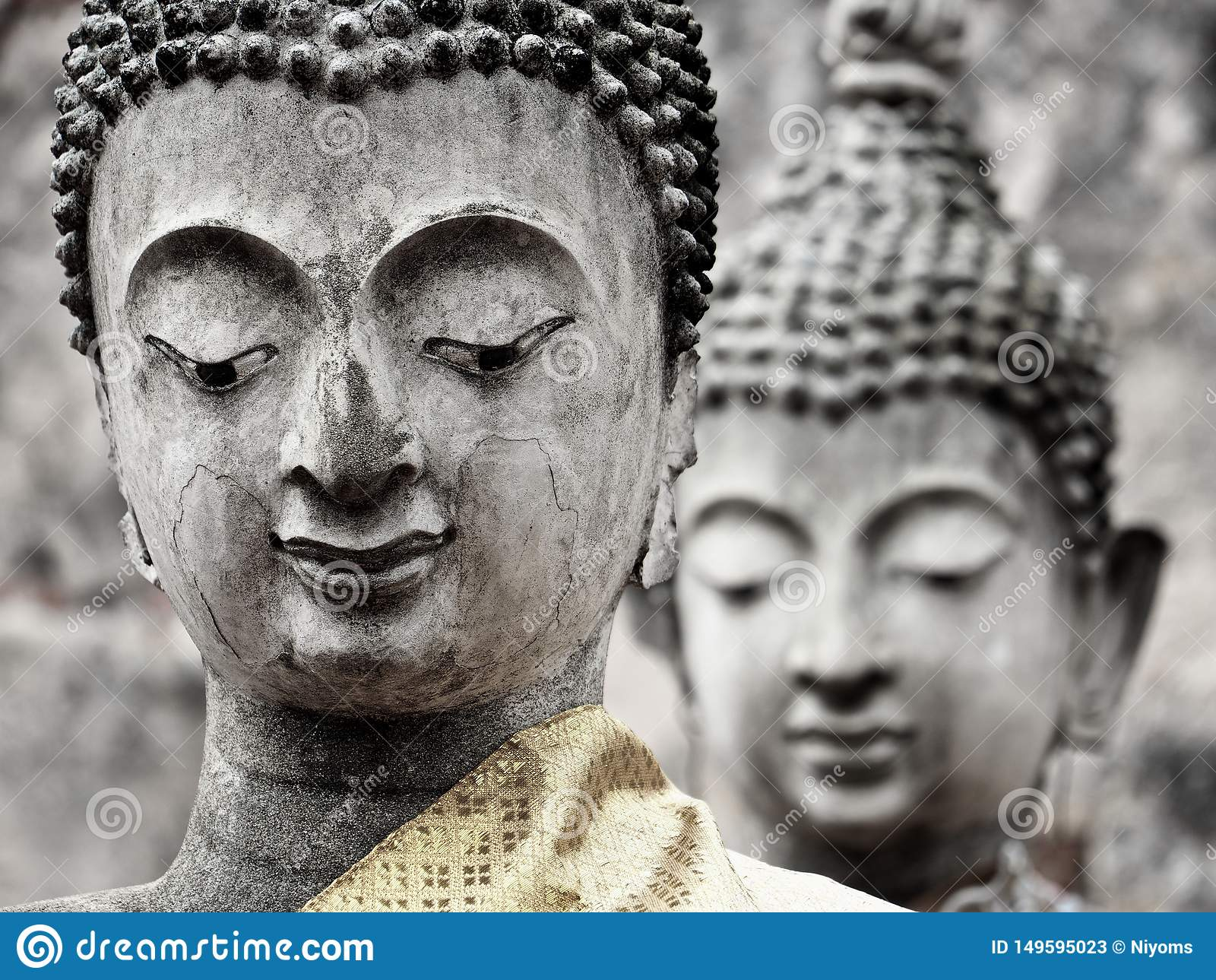 Close-up of two old Buddha statues of the ruined ancient temple