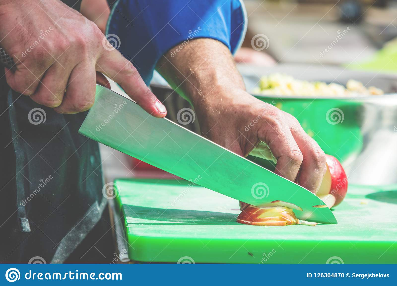 Close up of unrecognizable cook cutting onions and other vegetables with chef knife while working