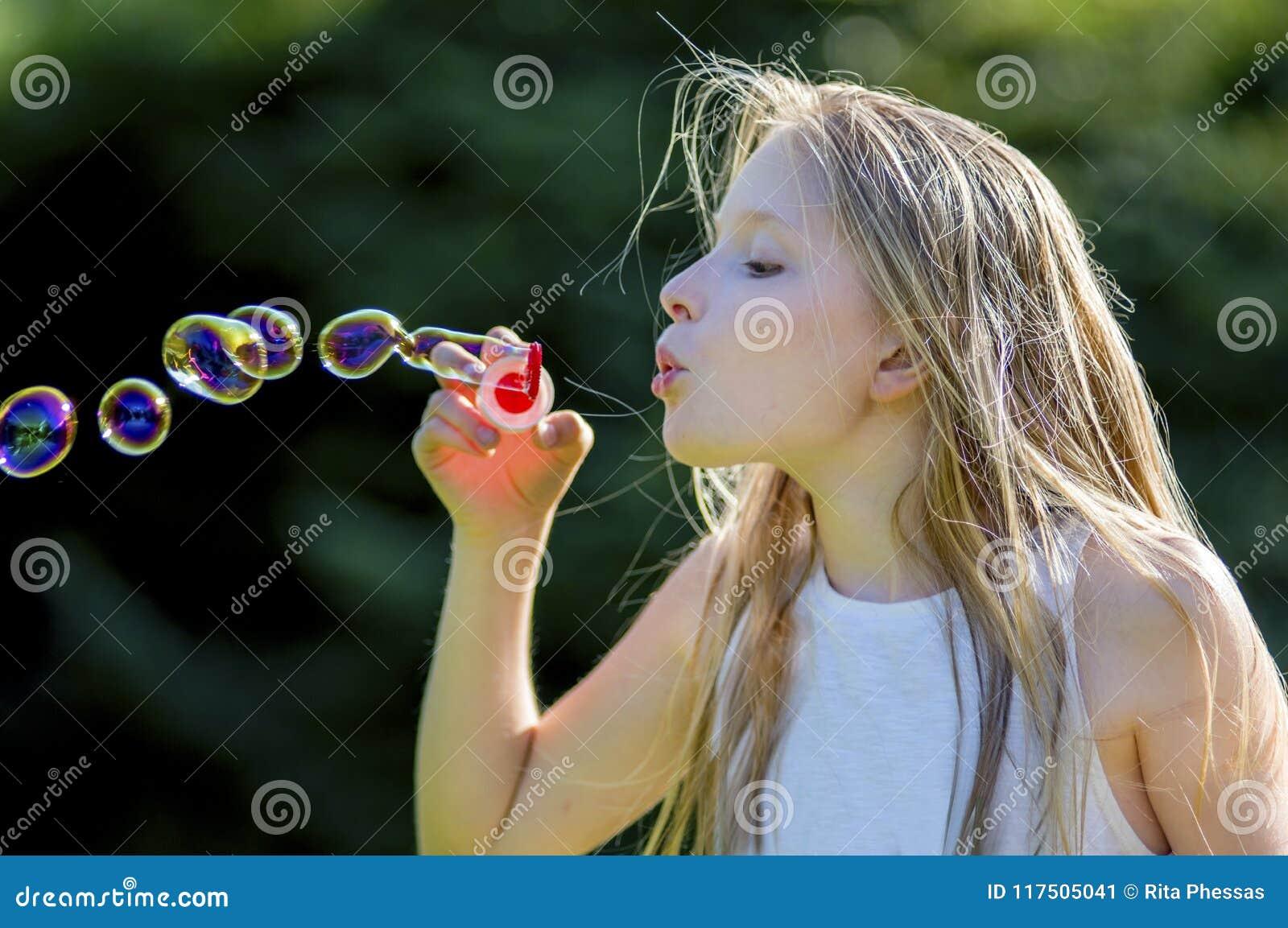 Close-up van bel-blazend jong meisje 11, met lang blond haar, die helder gekleurde bellen in de tuin blazen