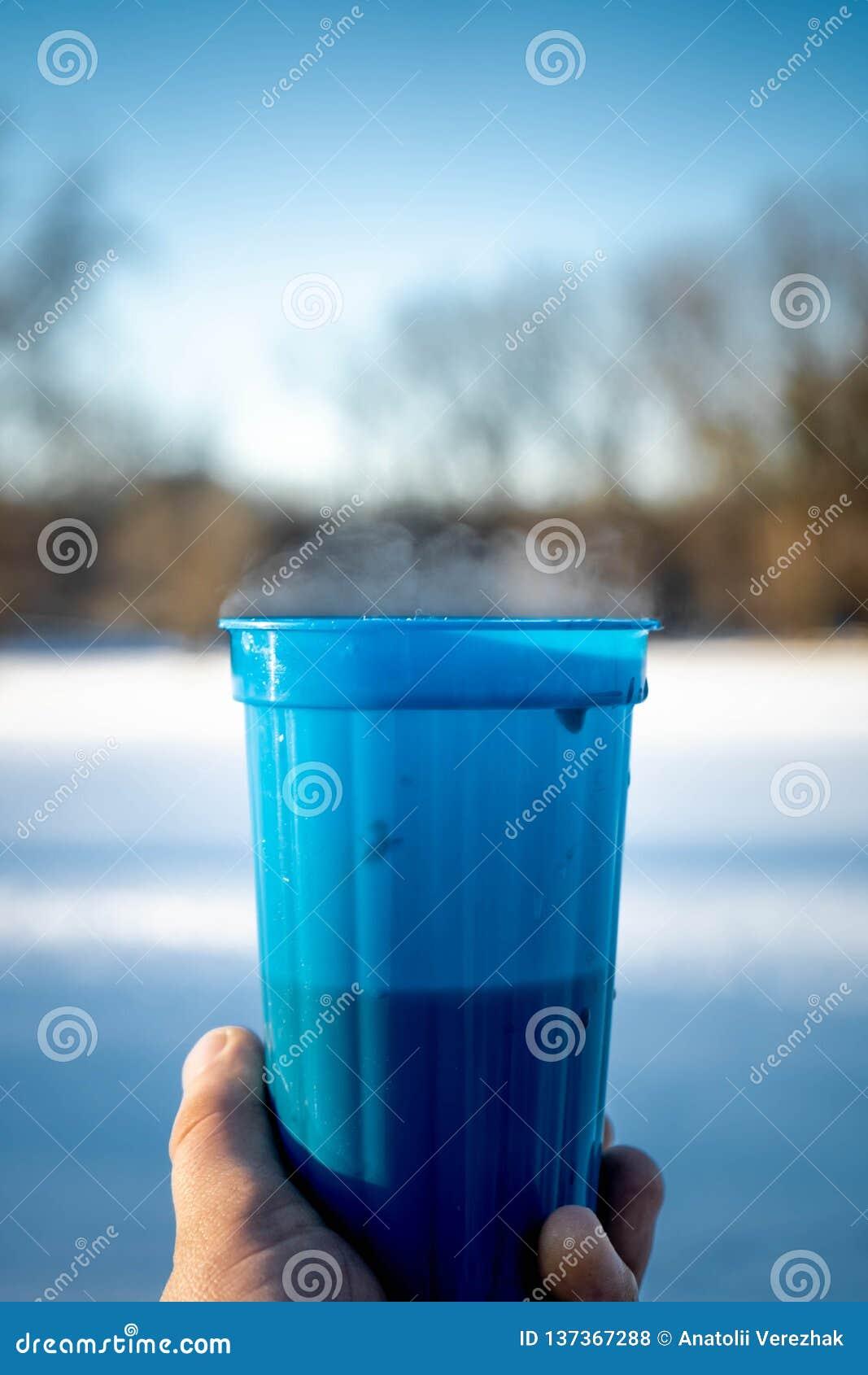 Close-up van blauwe plastic kop met hete wijn en dampholding ter beschikking