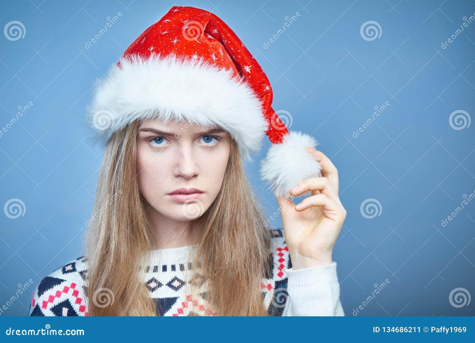 Close-up van Boze fronsende vrouw die Kerstmanhoed dragen