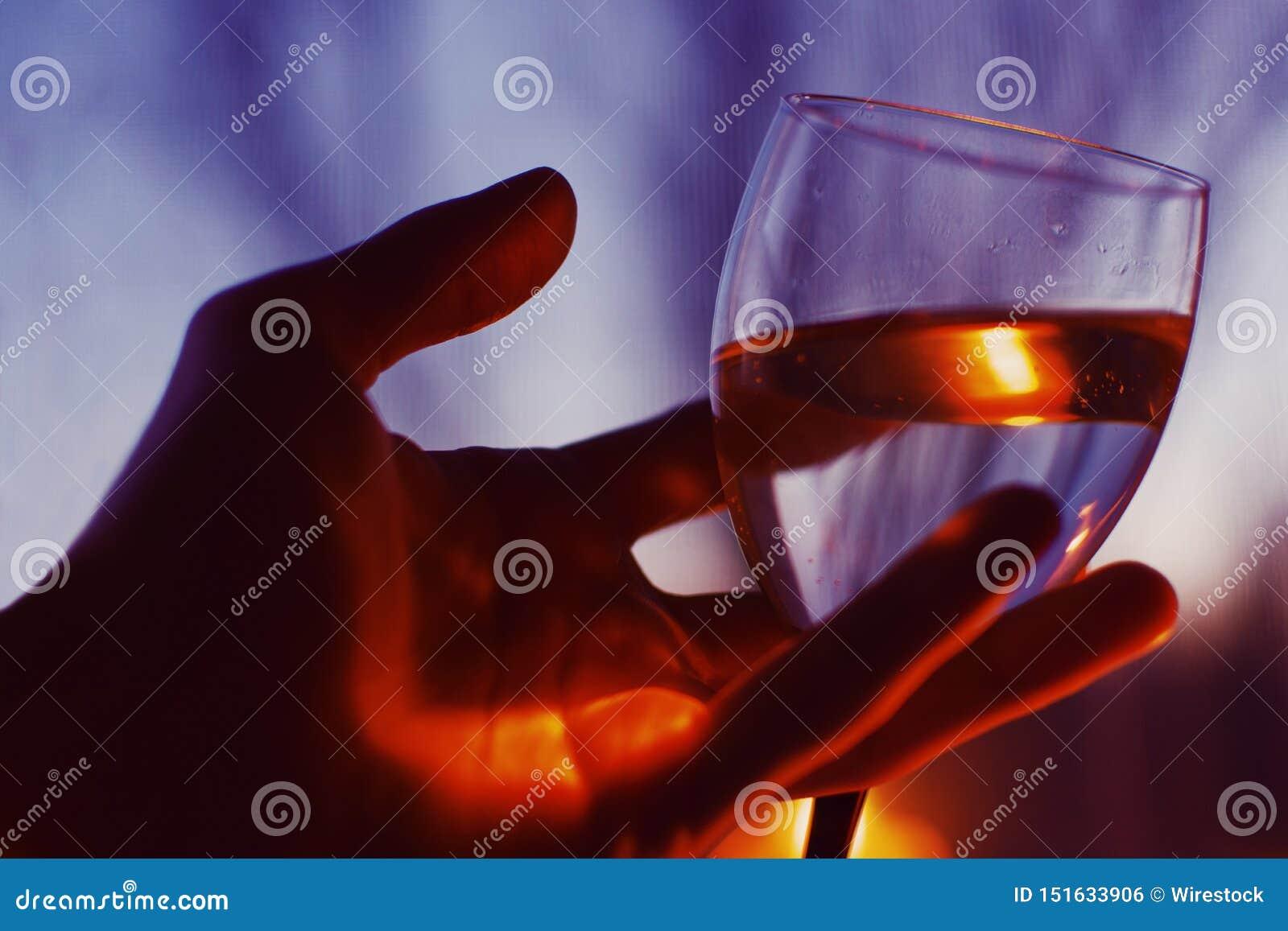 Close-up van de hand die van een persoon een glas witte wijn met een vage achtergrond houden