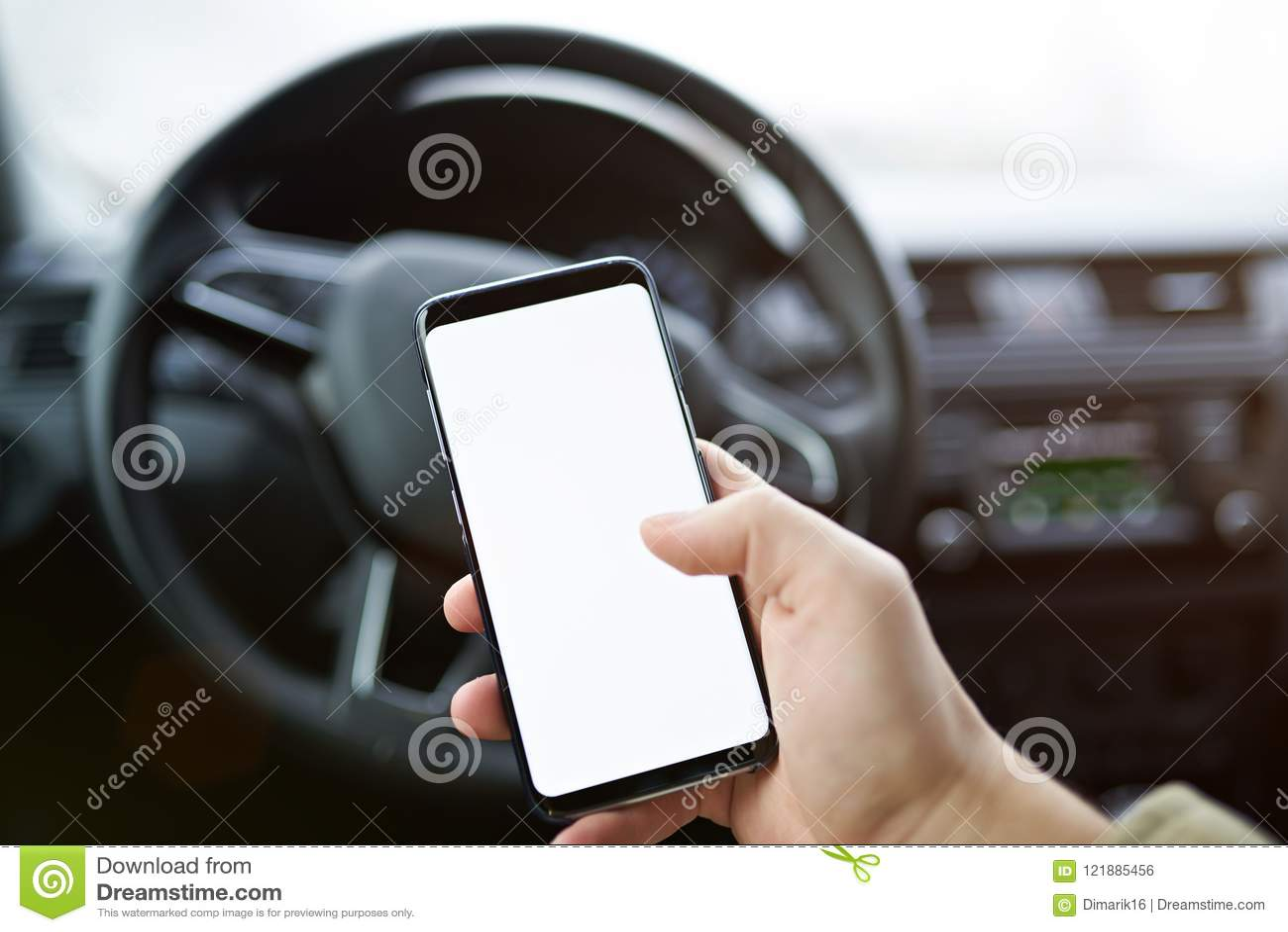 Close-up van de mens die smartphone in auto gebruiken