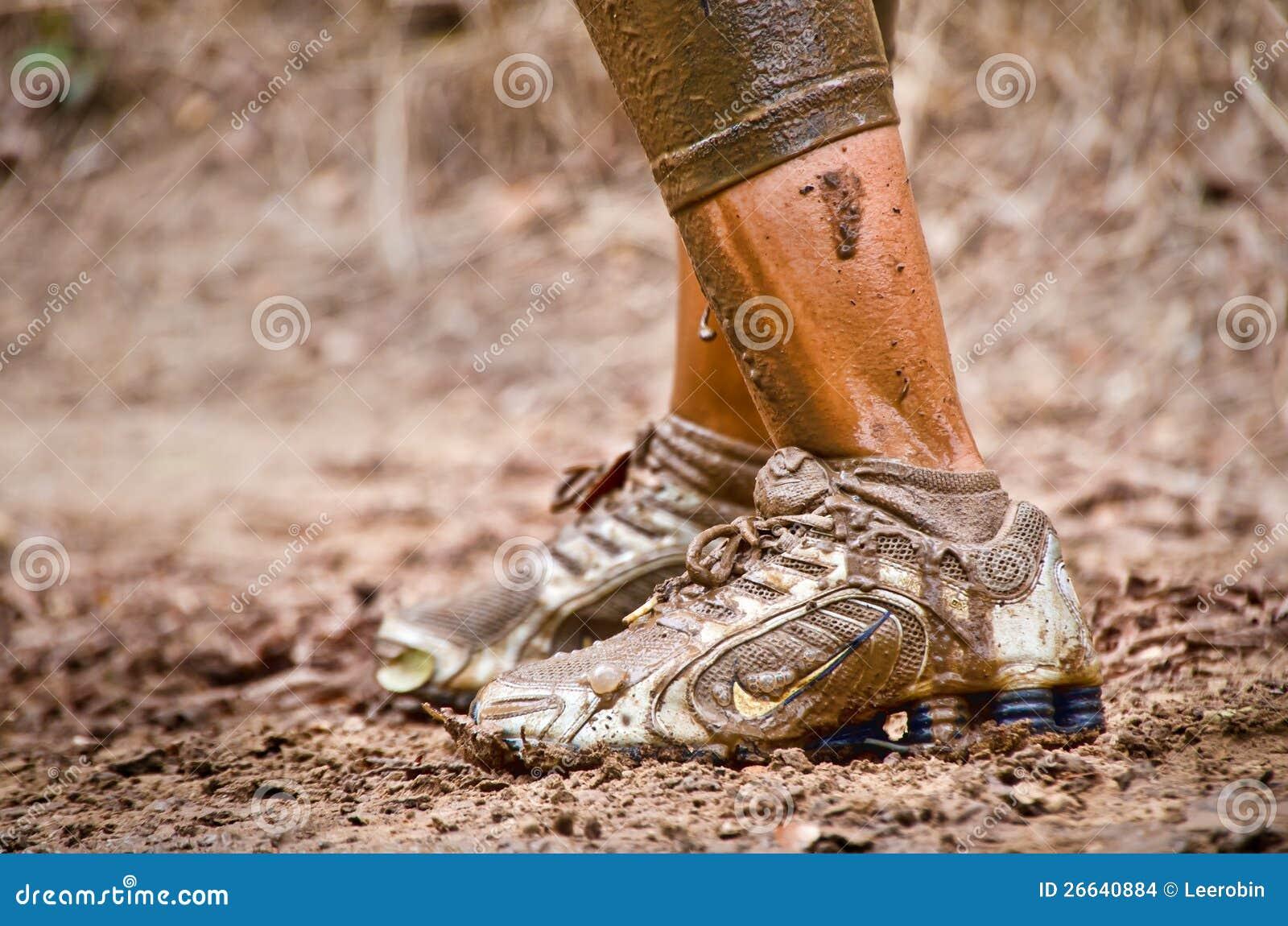 Close-up van de modderige voeten van de agent van het modderras