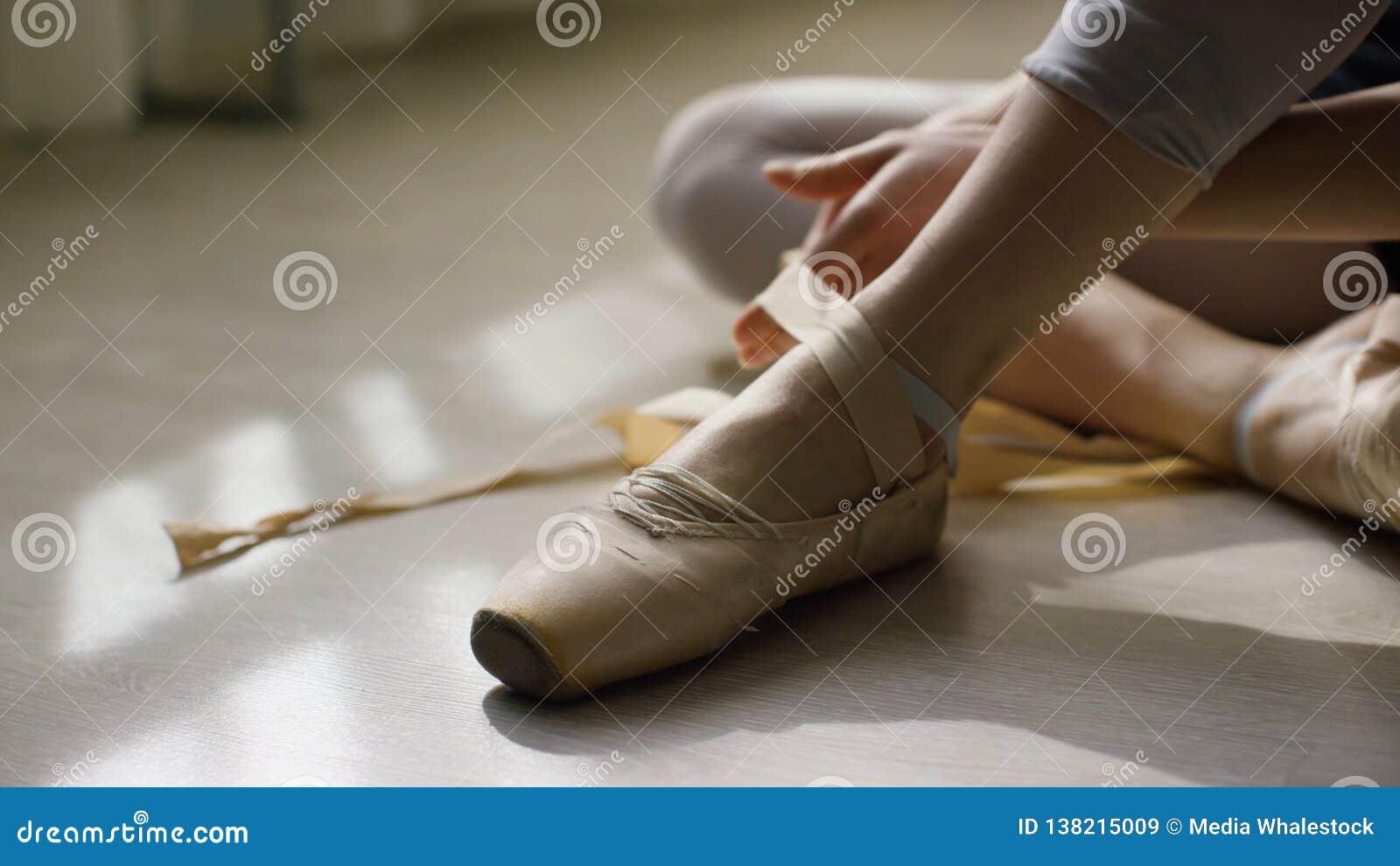 Close-up van de voeten van de ballerina Ballerina die voor opleiding, en bindend lint van pointeschoenen voorbereidingen treffen