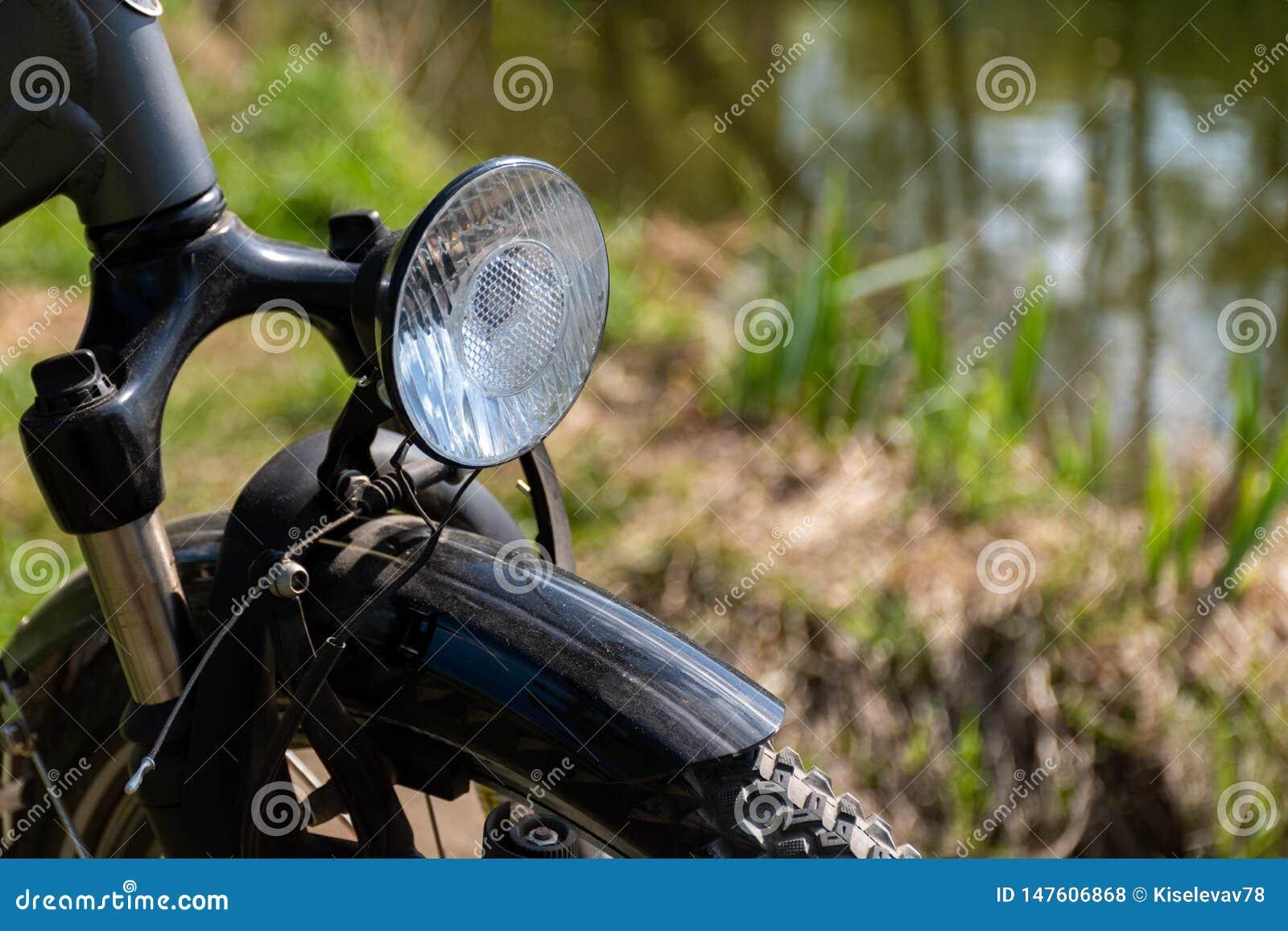 Close-up van de voorzijde van de fiets met een koplamp met een vage achtergrond van gras en vijver