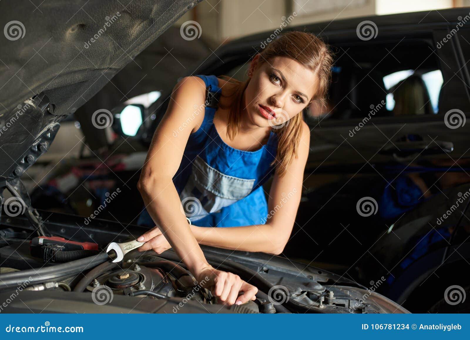 Close-up van donkerbruine vrouwelijke werktuigkundigen die of een auto herstellen inspecteren