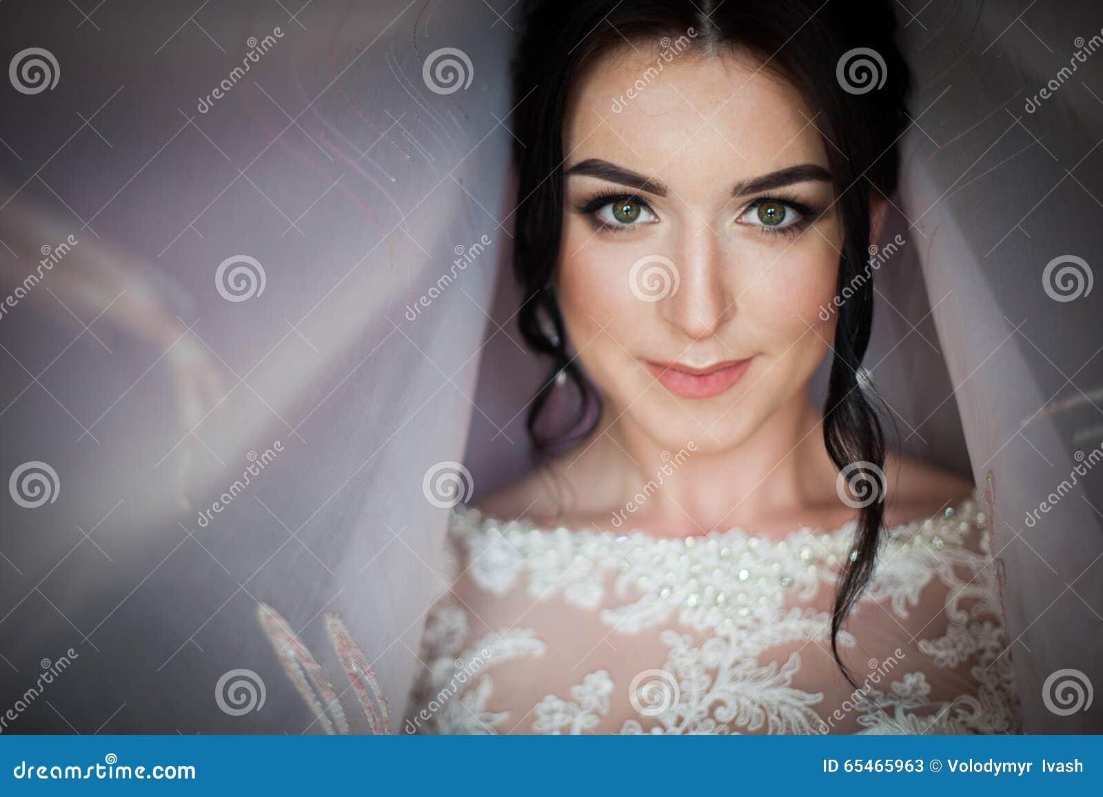 Close-up van een elegante, donkerbruine bruid in uitstekende witte dres wordt geschoten die