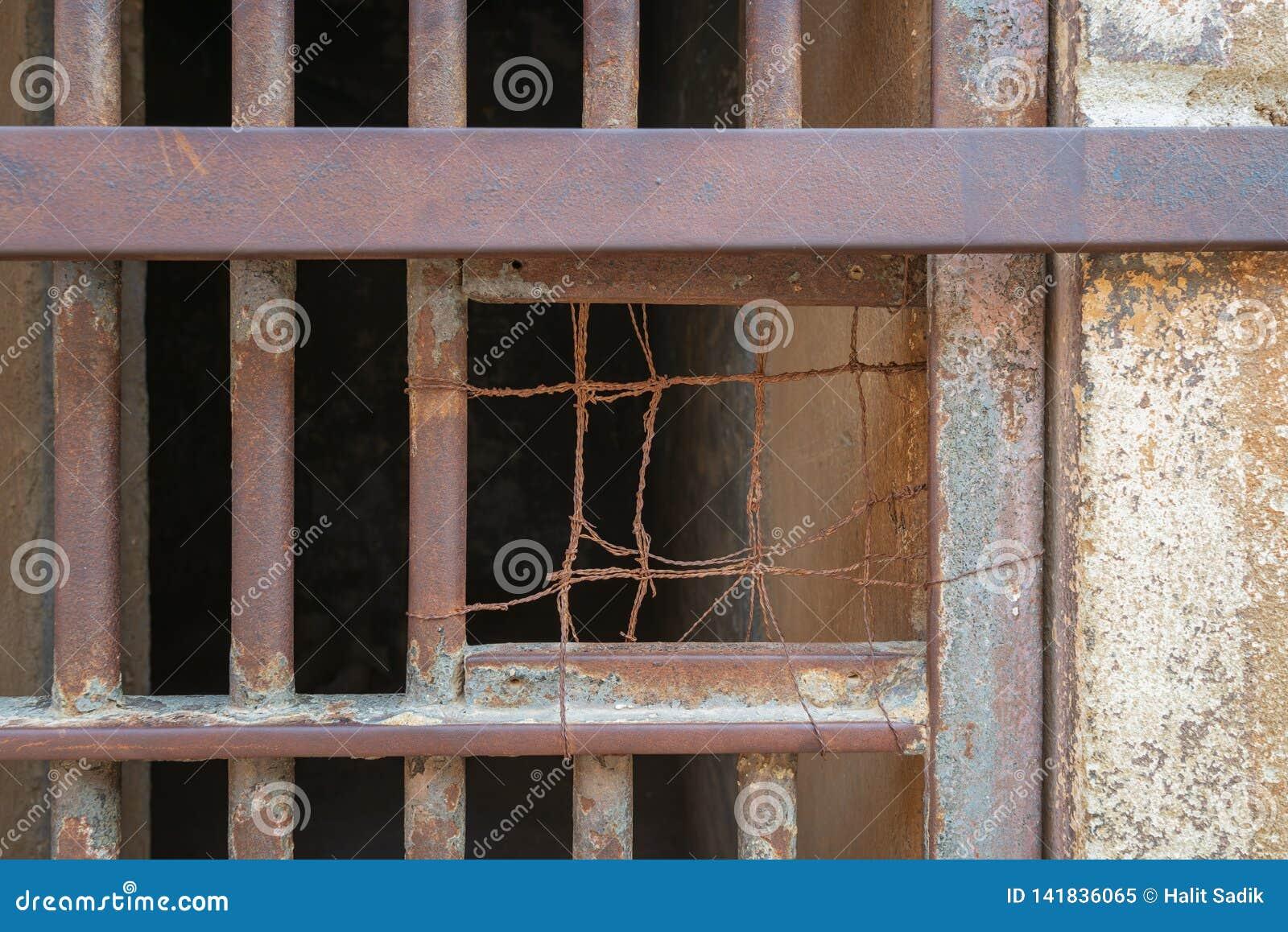 Close-up van een gesloten geroeste ijzerbars van celdeur in gesloten verlaten gevangenis