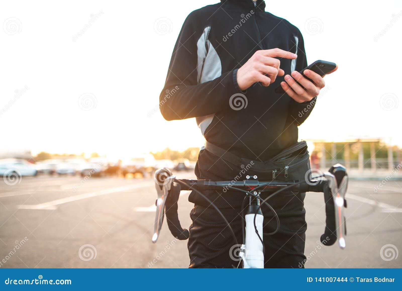 Close-up van een hand met een smartphone bij een mens met een fiets De rust van de fietsruiter en het gebruiken van een smartphon