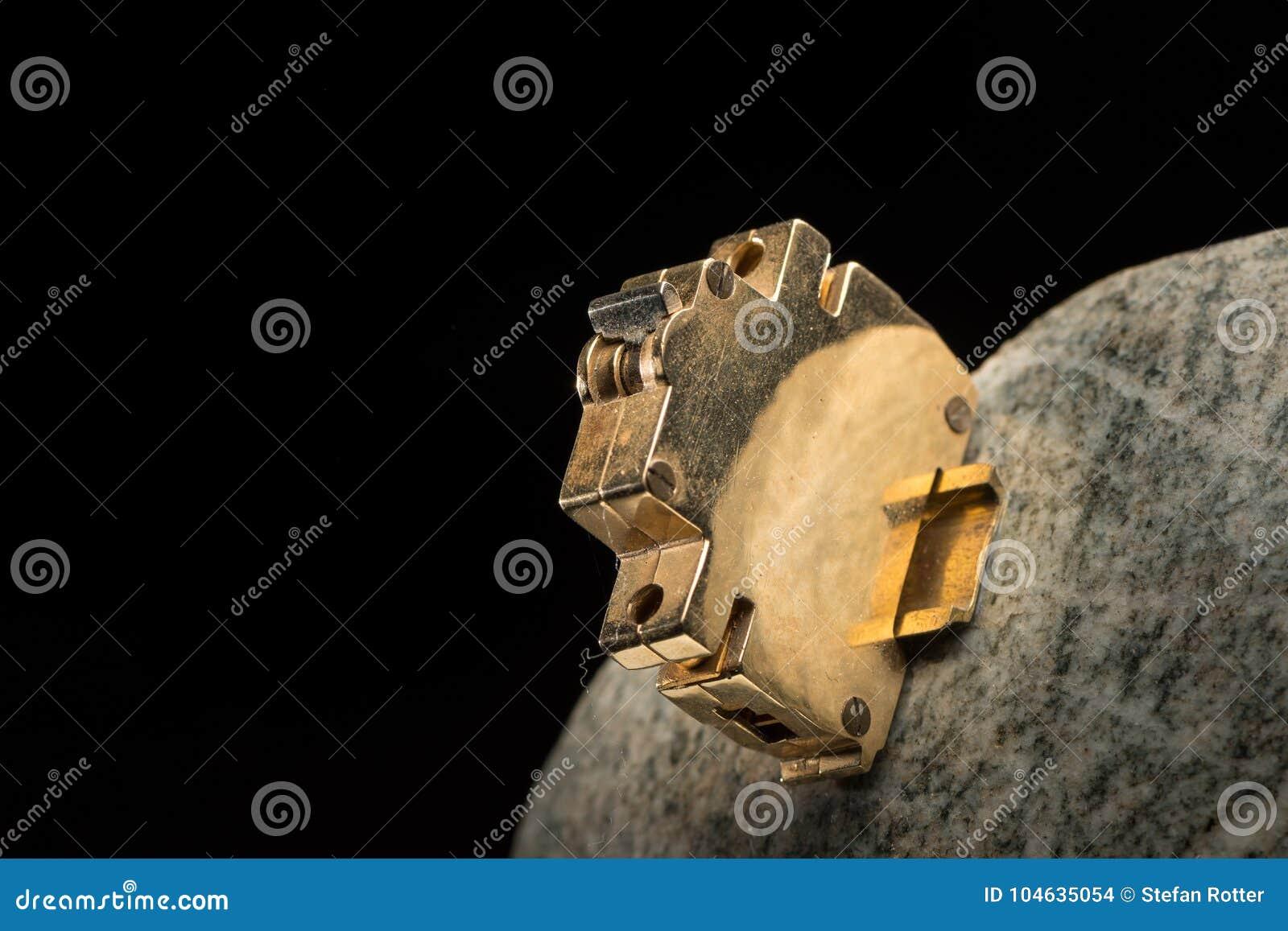 Close-up van een klein gouden model van een stroomonderbreker