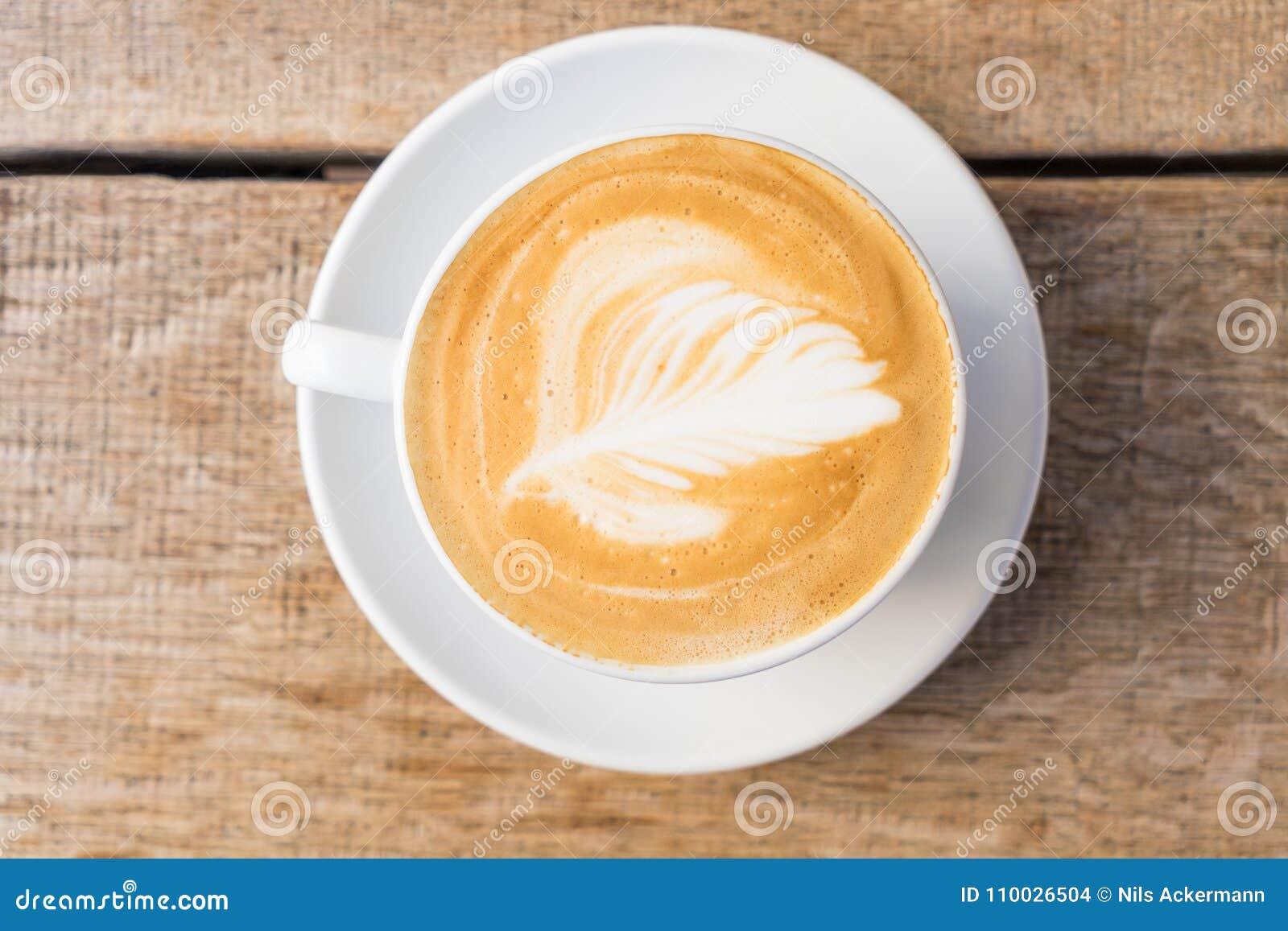 Close-up van een kop van koffie/cappuccino met schuim en baristakunst op houten lijst