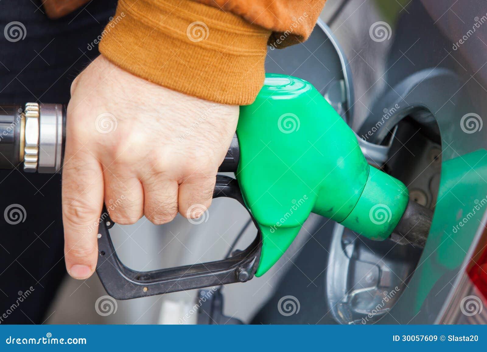 Mens die de auto met brandstof op een benzinebenzinestation opnieuw vullen