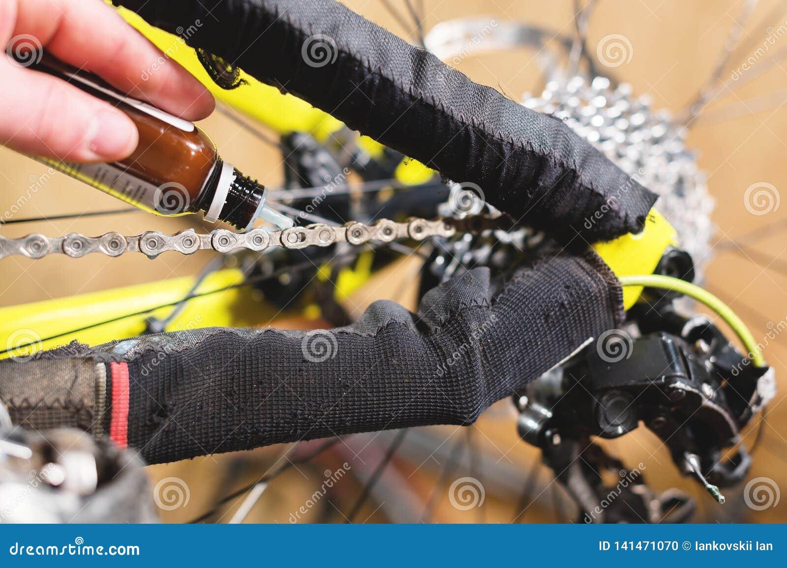 Close-up van een man hand, door meesters wordt het geleid, smeert de fietsketting van een bergfiets met een speciaal smeermiddel