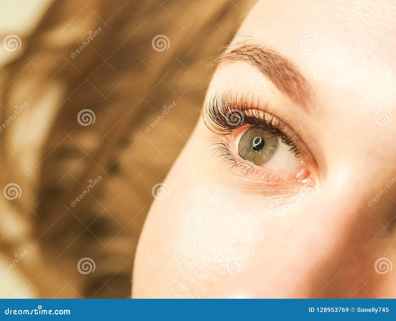 Close-up van een meisjes` s oog met zwepen Het concept het geven voor de ogen, wimperuitbreidingen in de salon