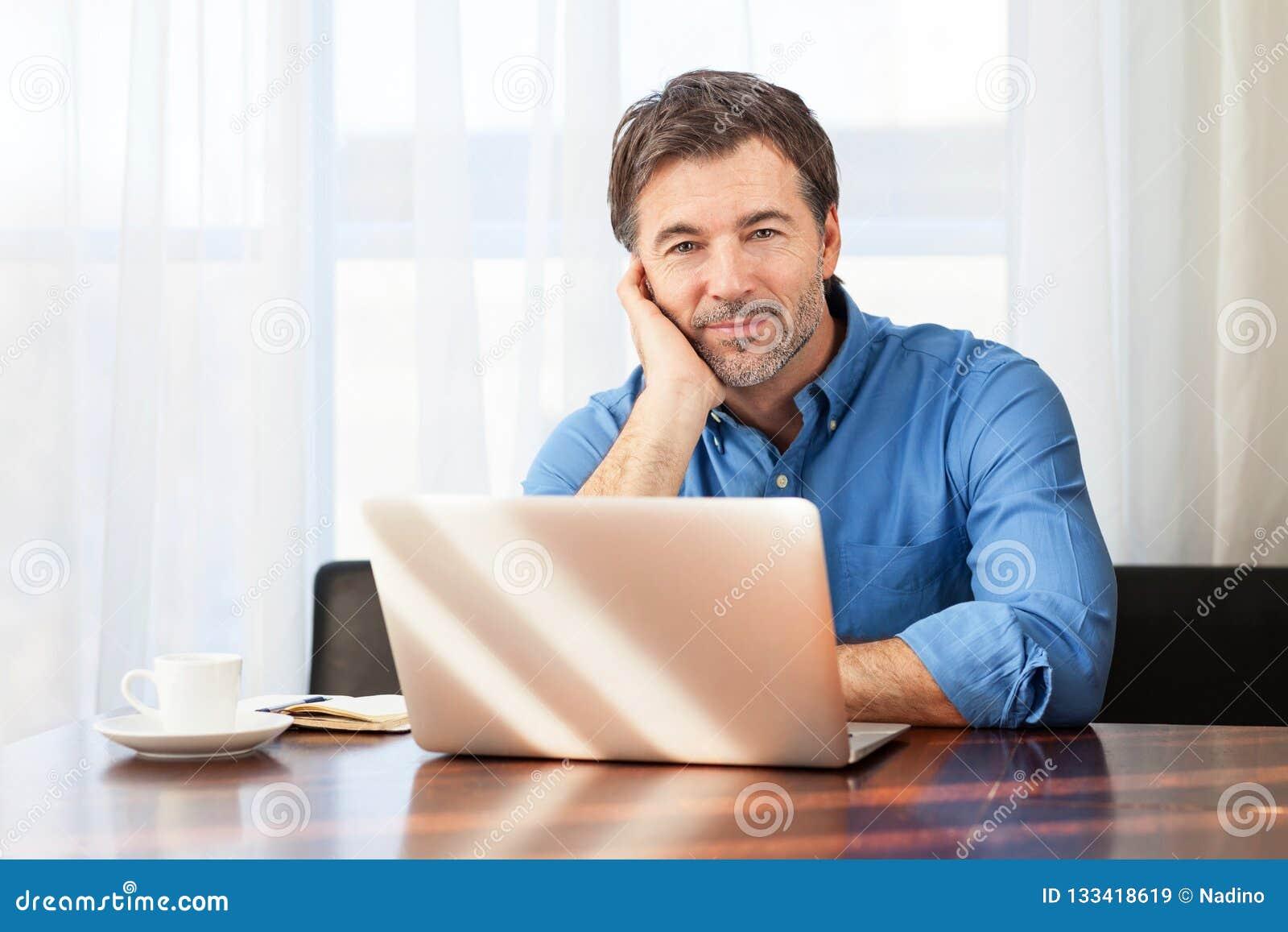 Close-up van een mens op middelbare leeftijd, bored op een gordijnenachtergrond op het kantoor